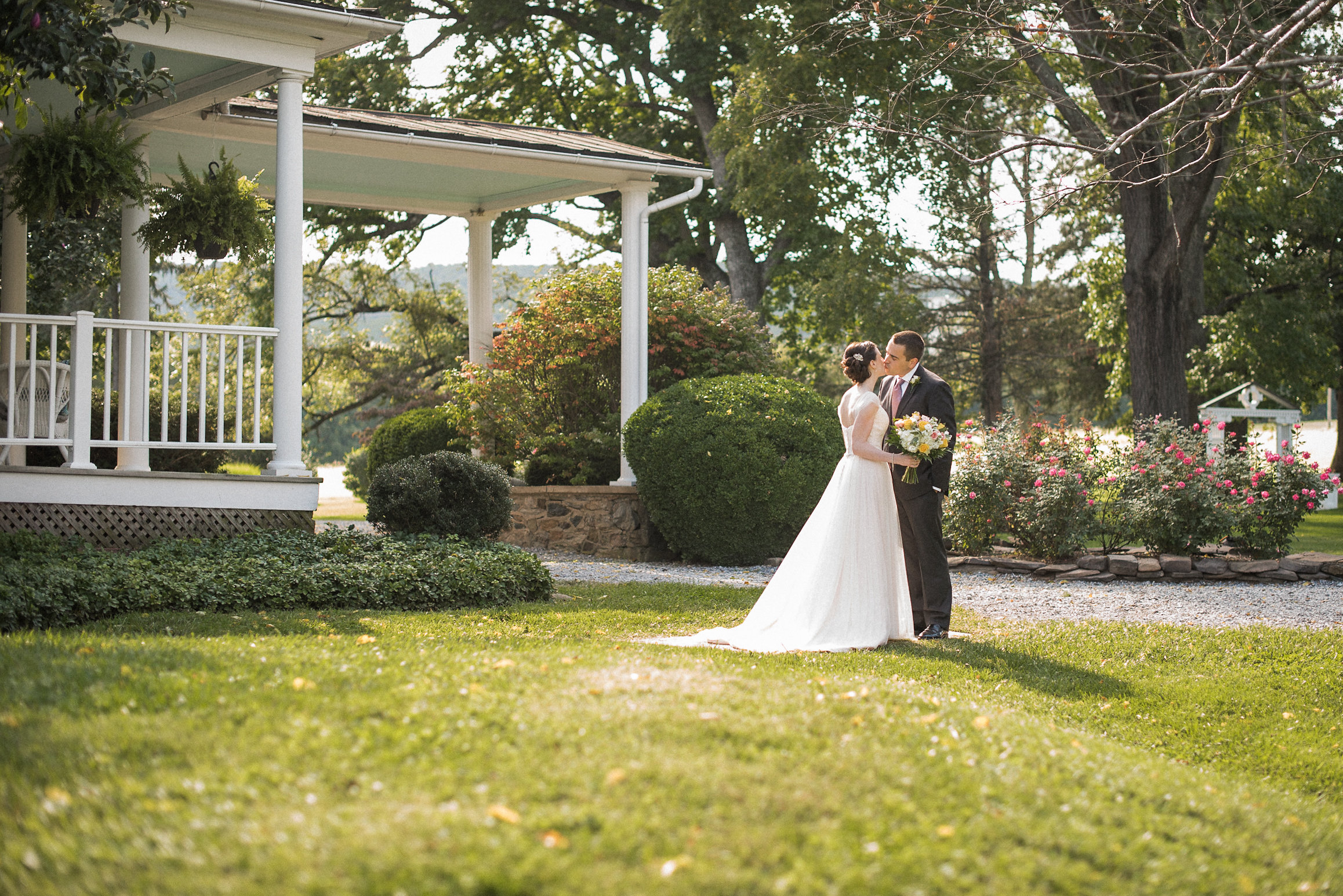 Bride and groom kissing on front lawn
