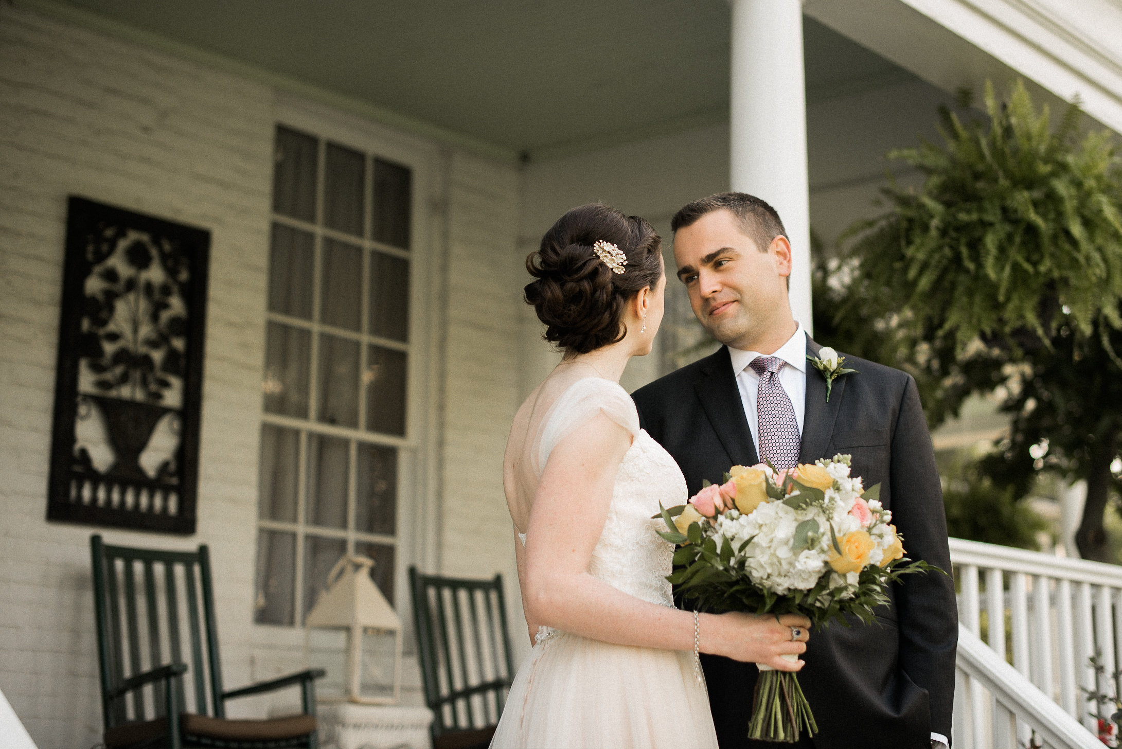 Groom looking at bride on porch