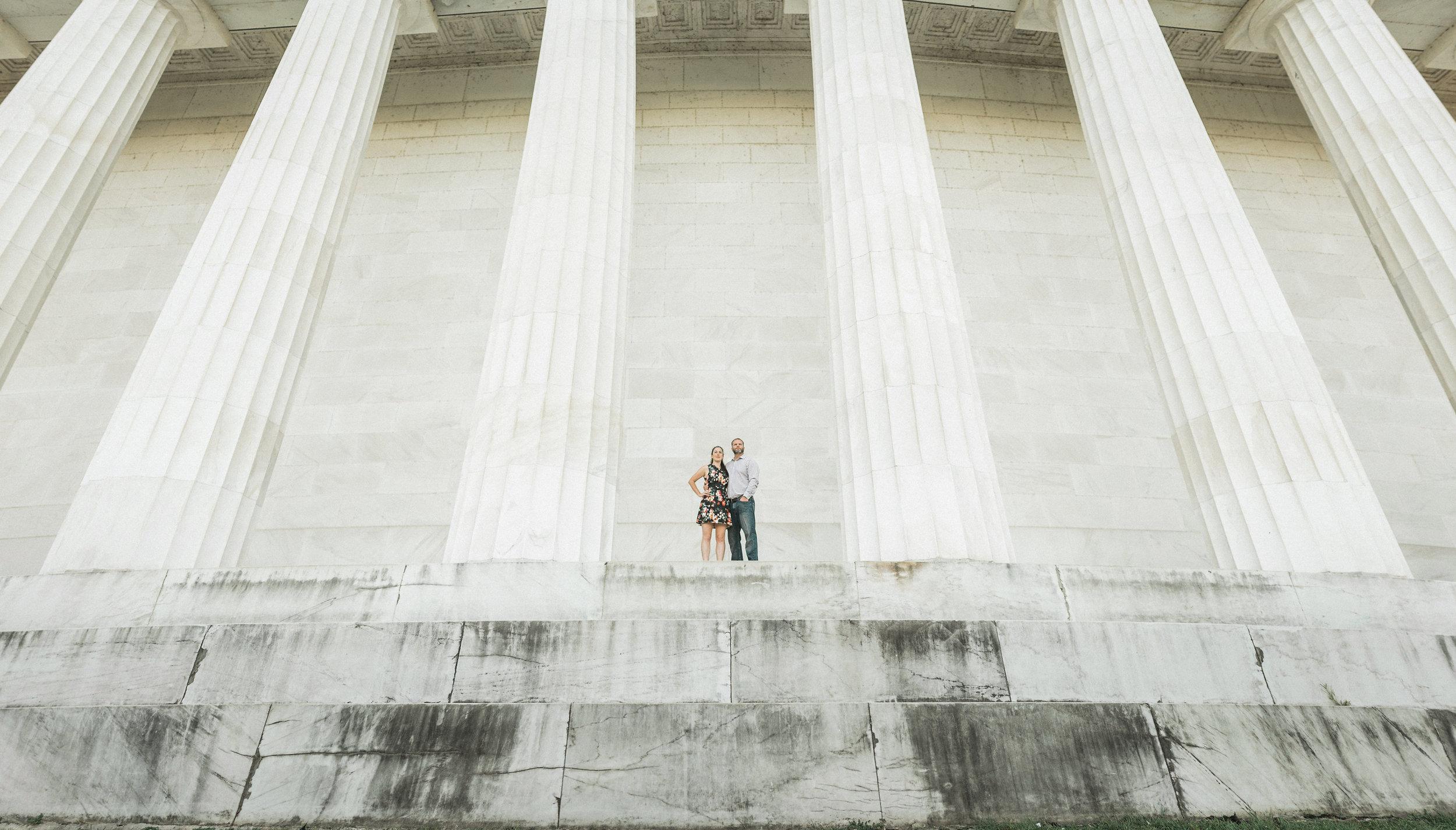 Couple standing between marble pillars