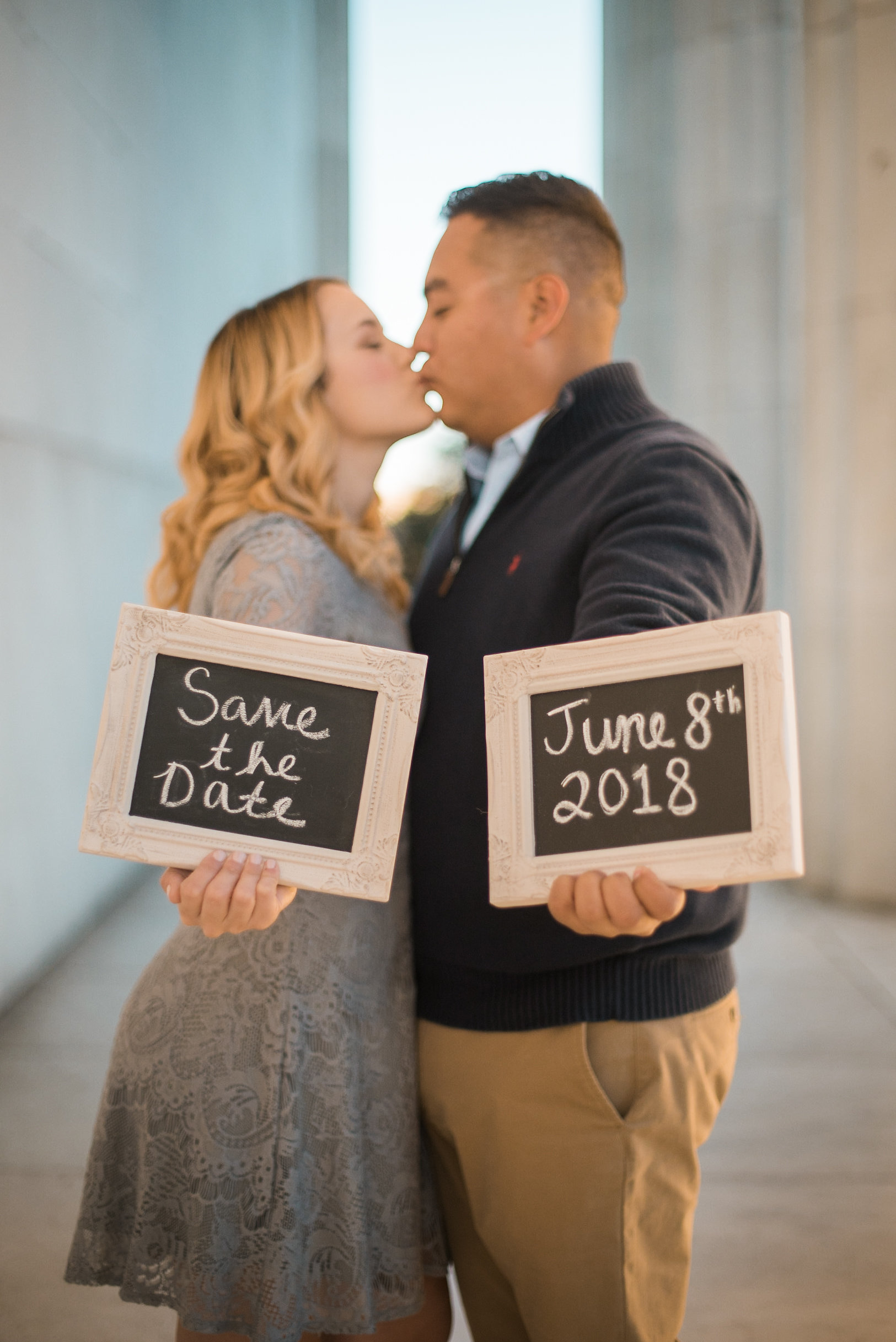 Couple holding sign and kissing