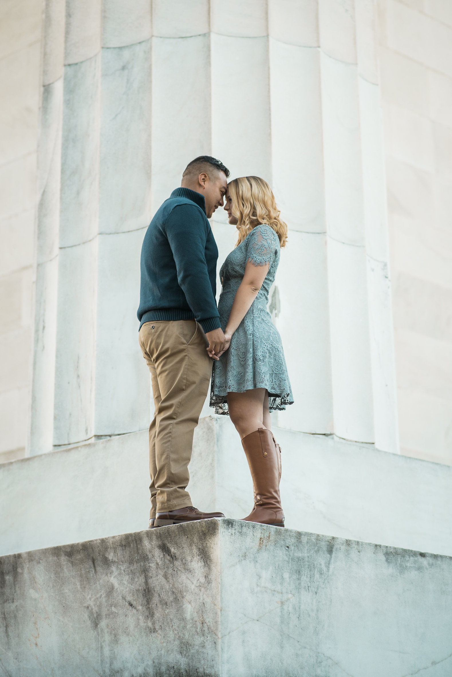 Couple standing by marble pillar