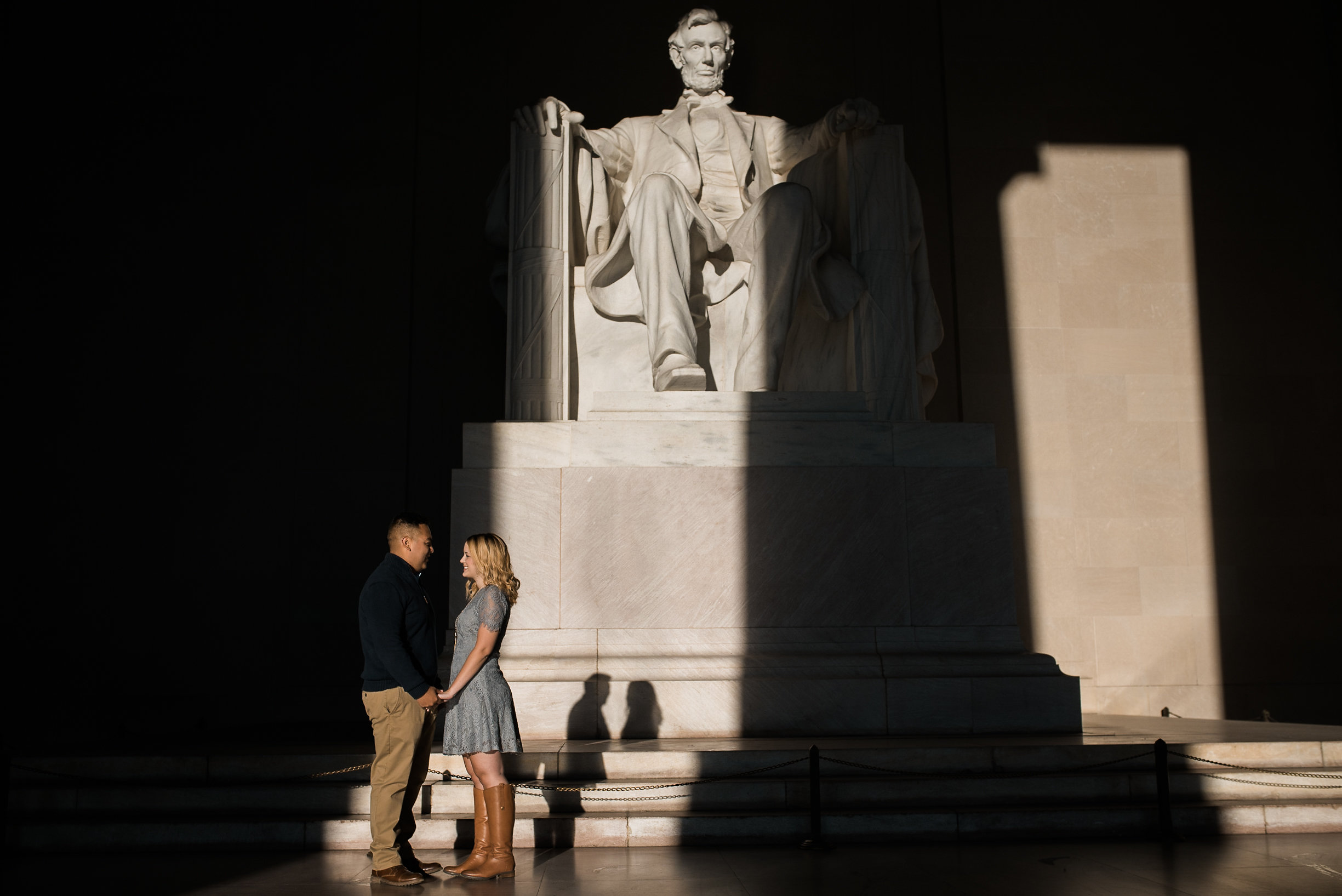 Couple standing in shadows at Lincoln Memorial