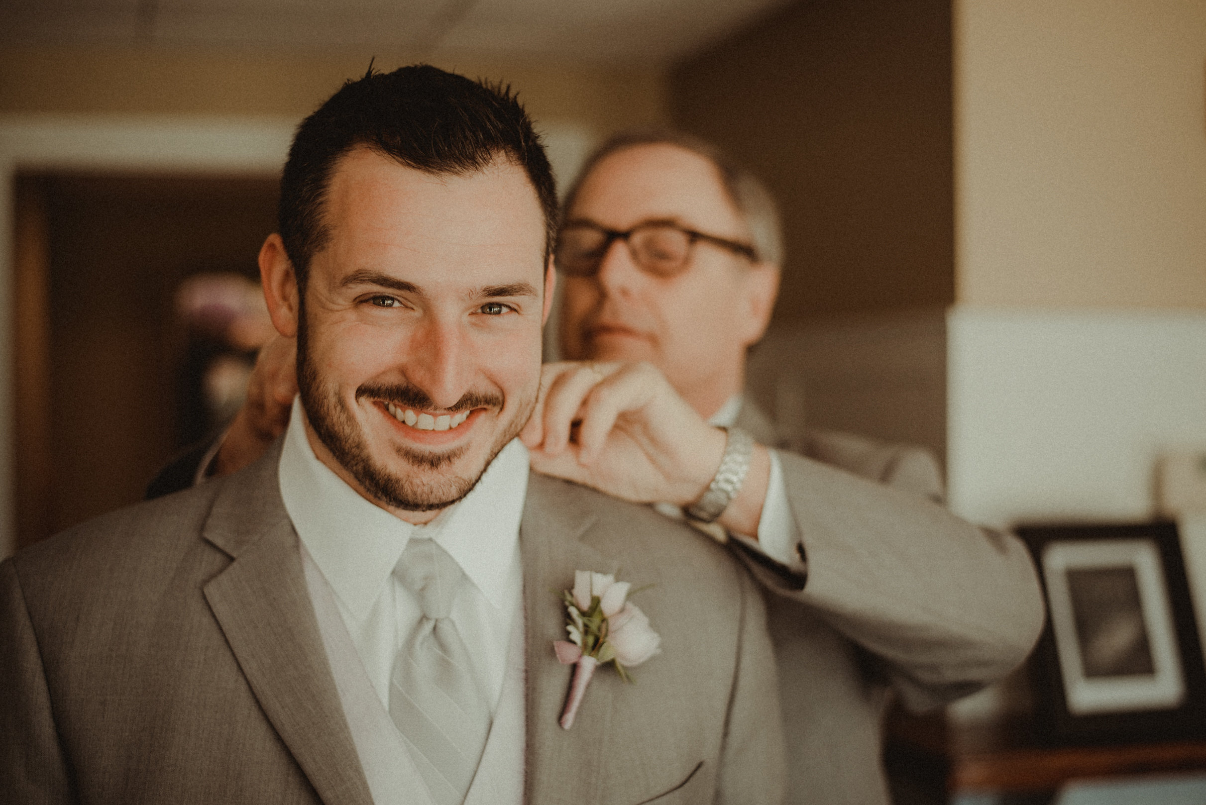 Groom's father helping with tie