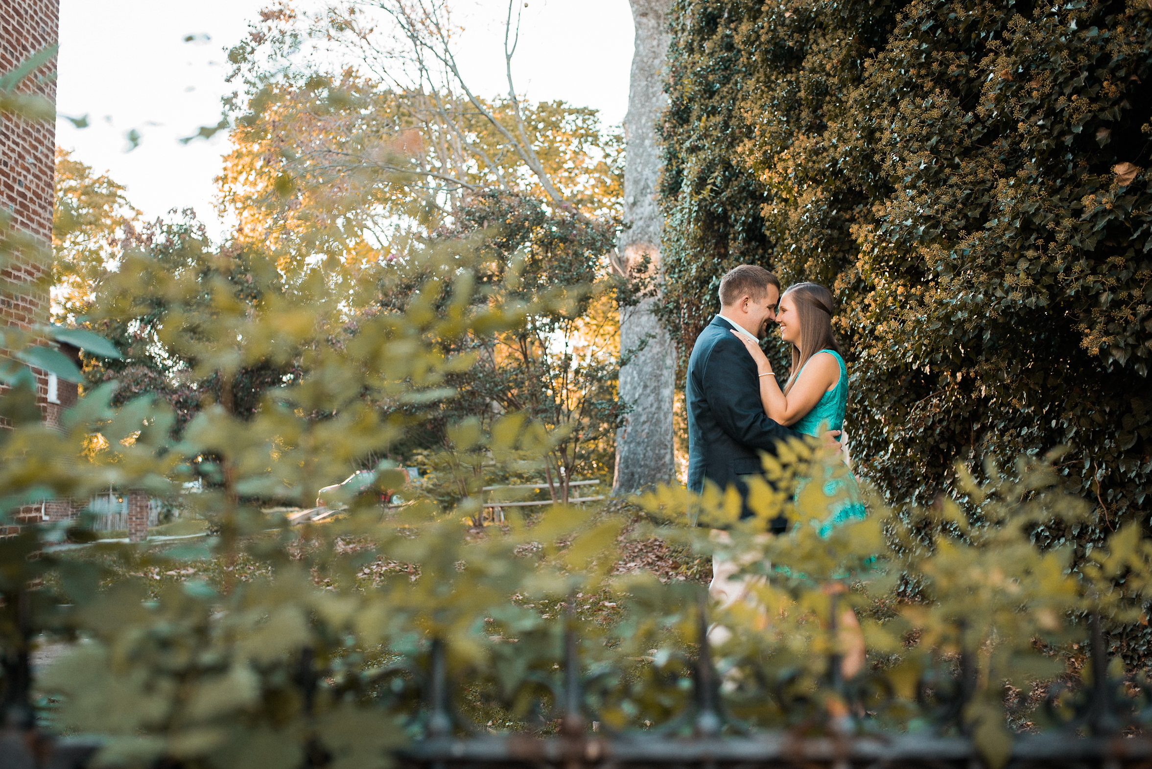 Couple kissing behind plants
