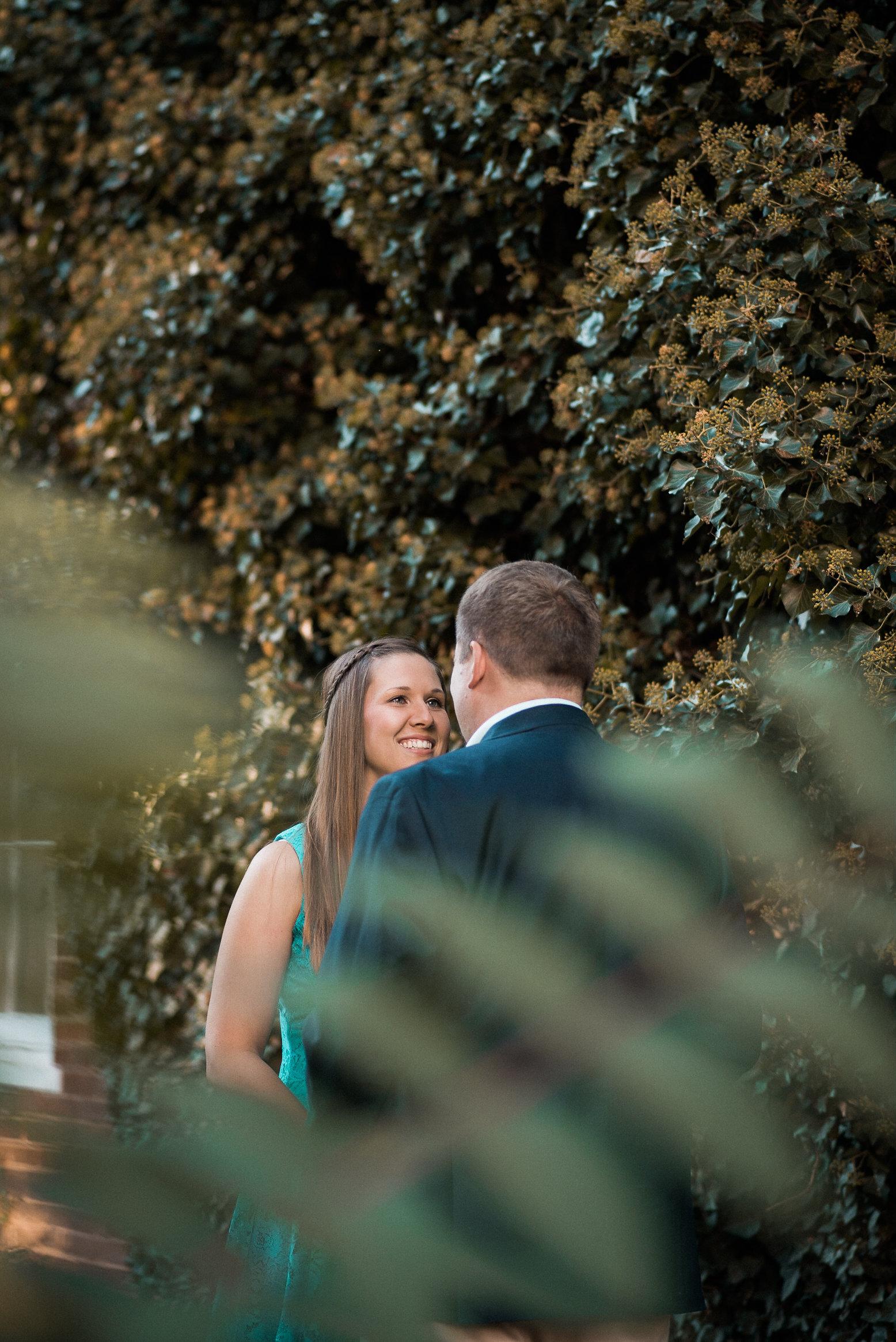 Couple seen behind fern