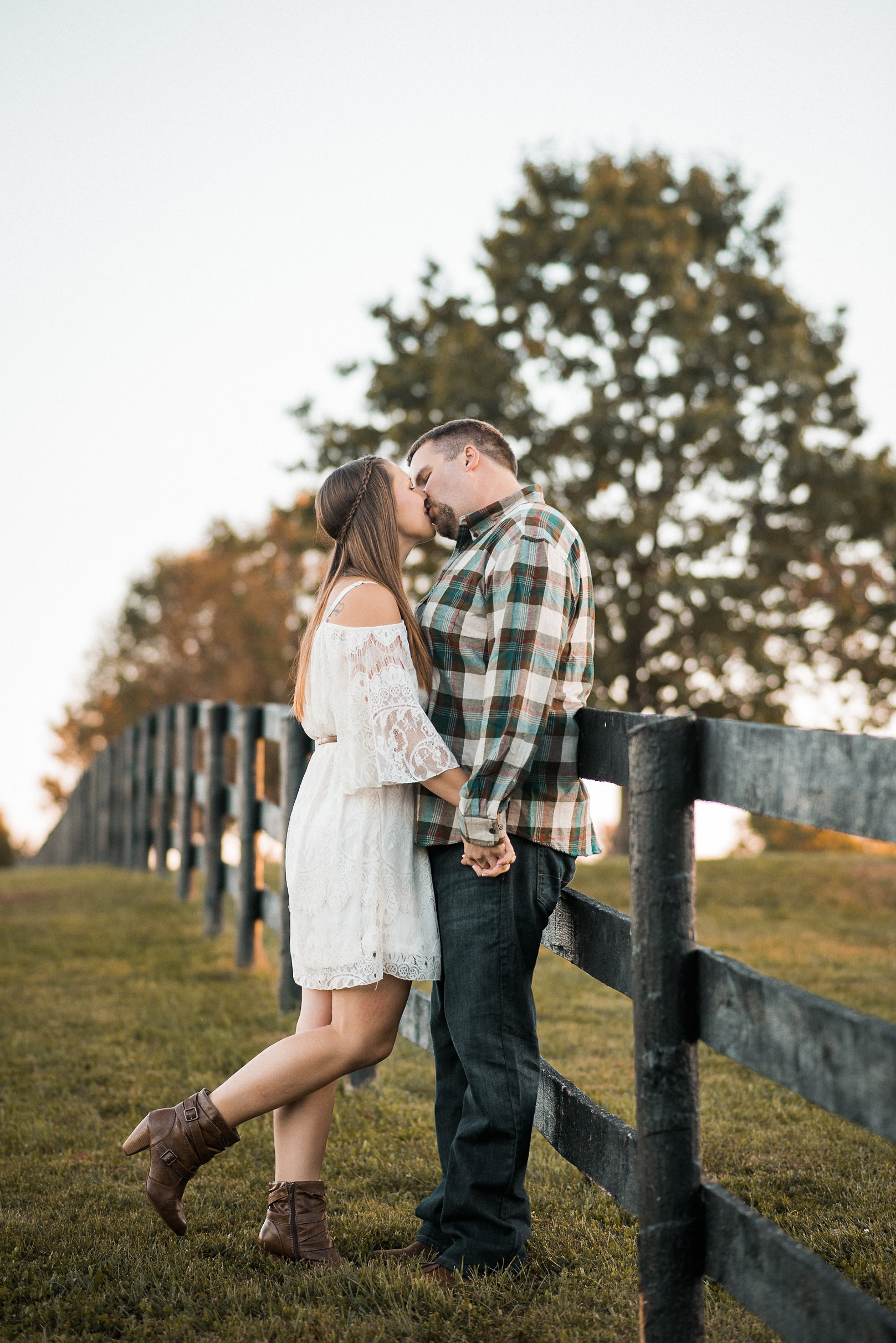Couple kissing against fence