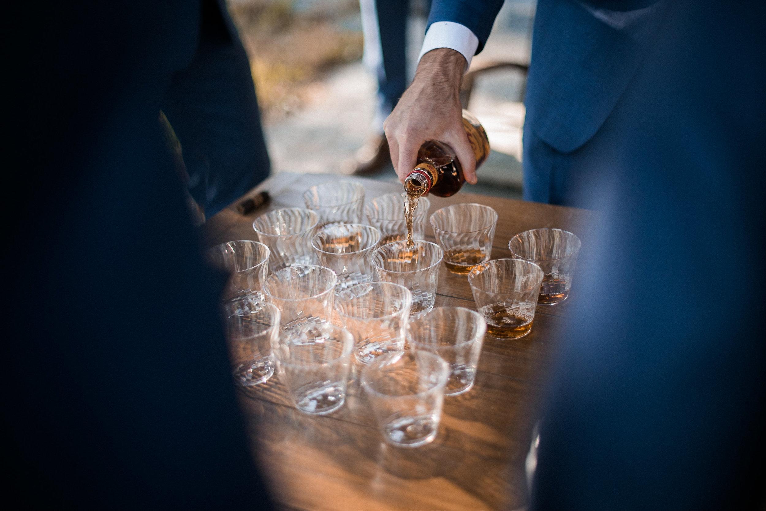 Groomsman pouring drinks