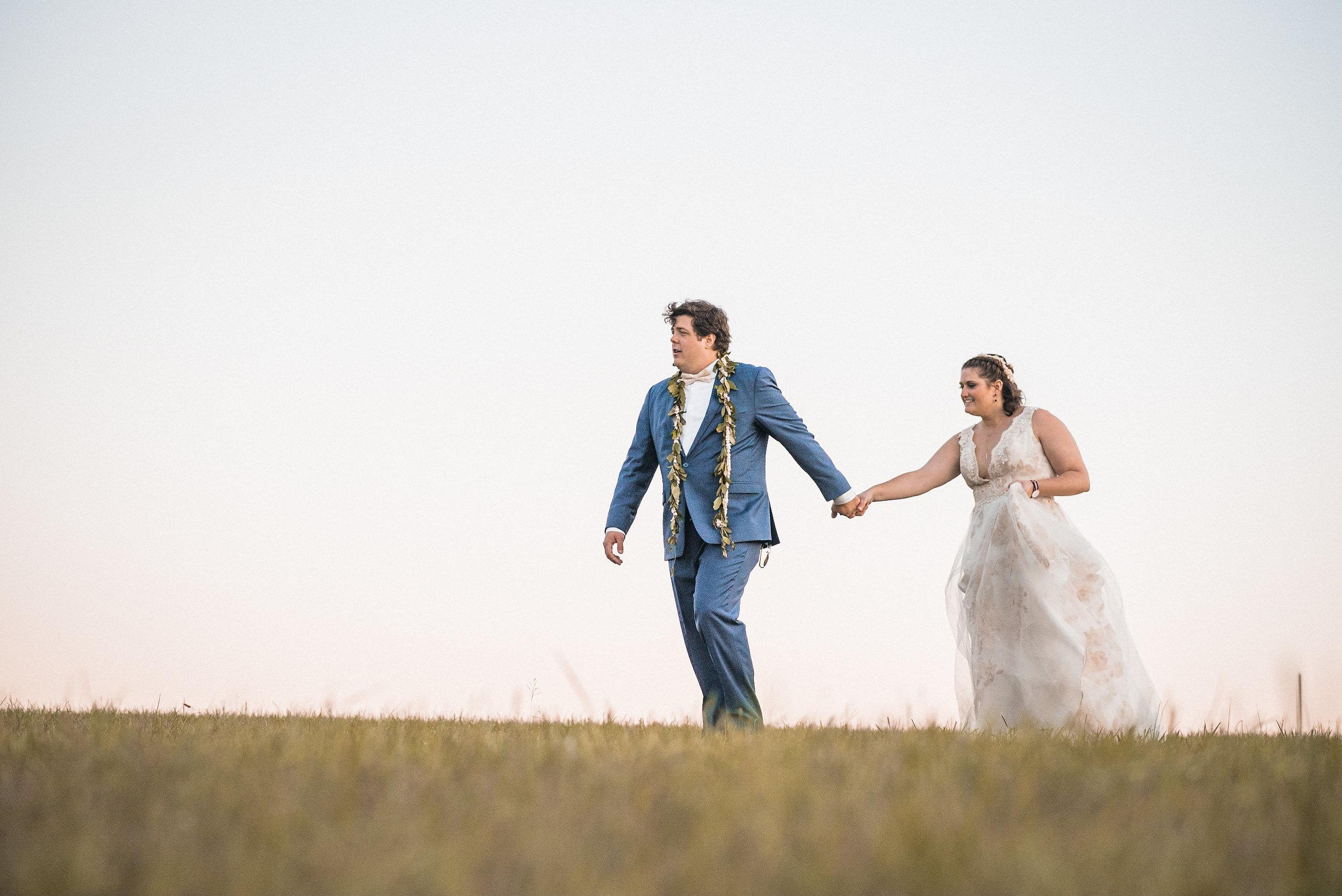 groom leading bride across field