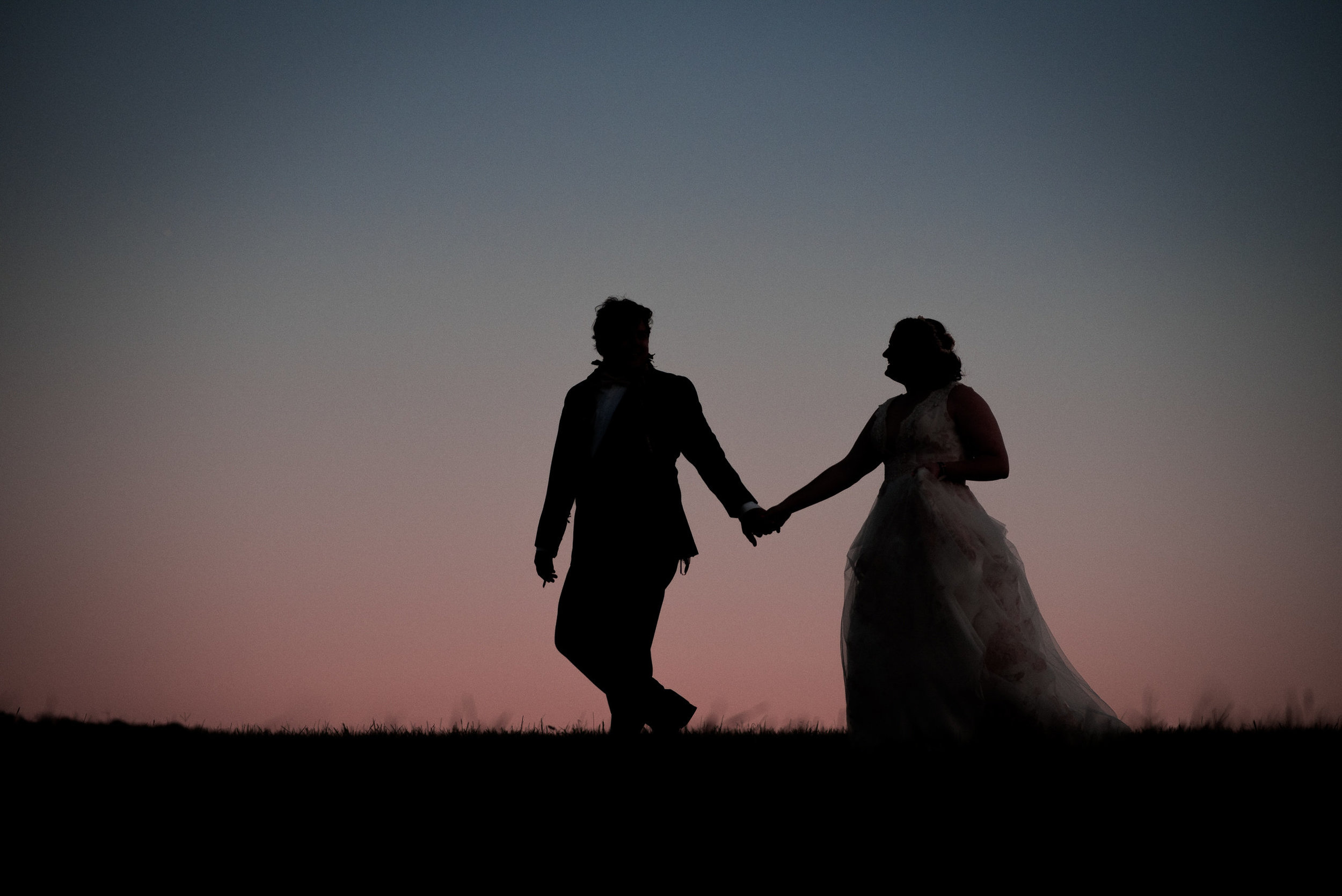 bride and groom in field at dusk