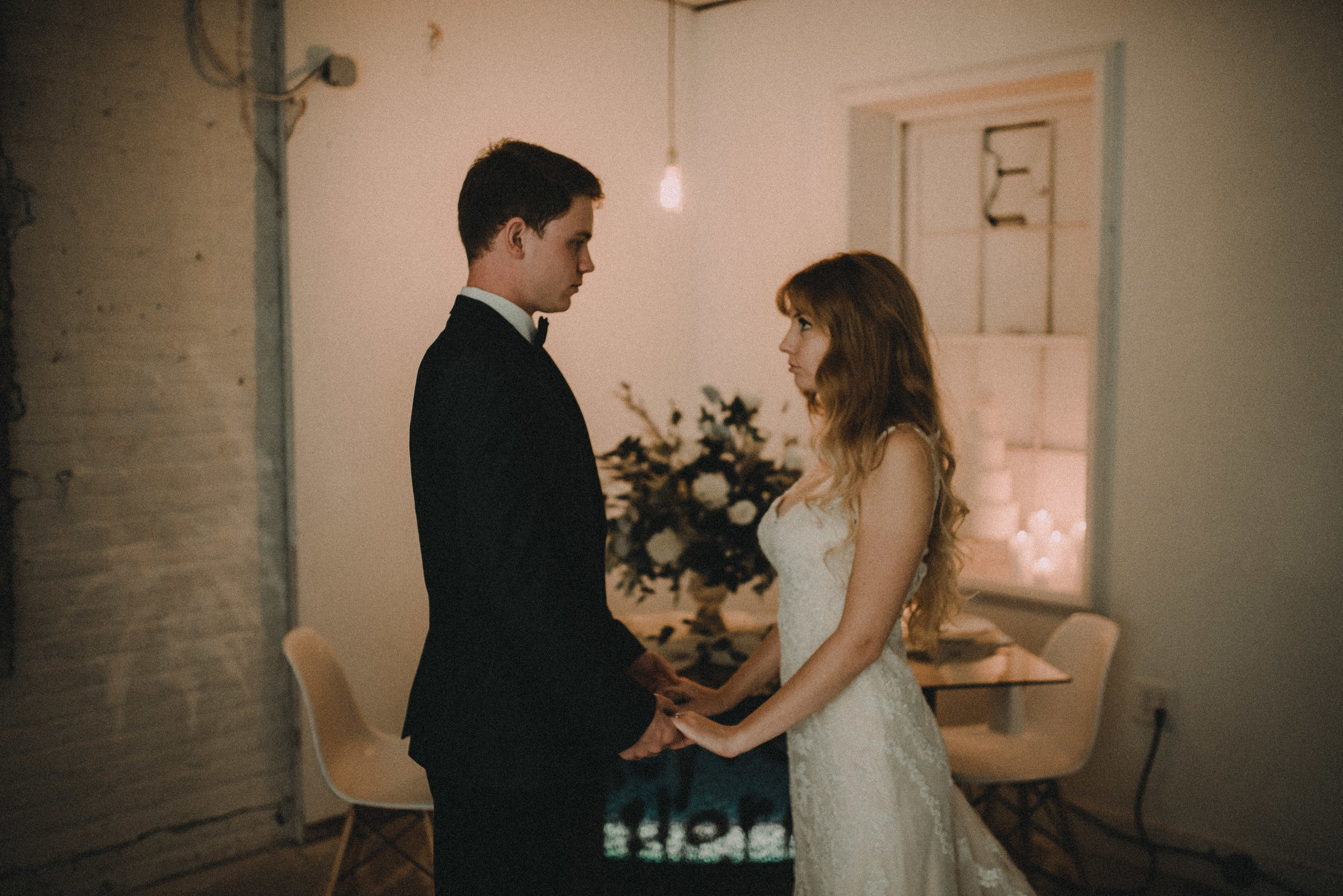 Bride and groom holding hands in front of haunted tv