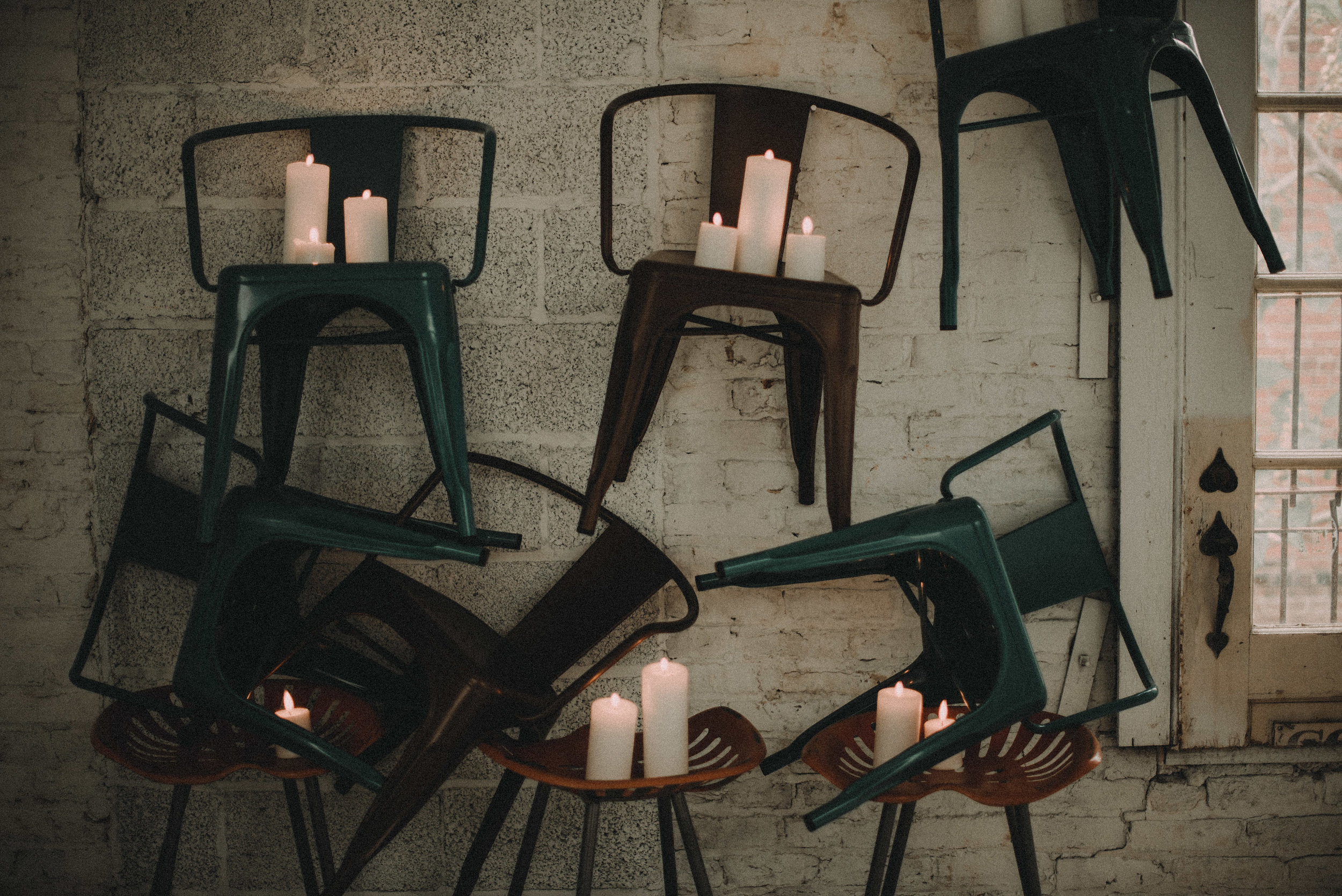 Chairs levitating on brick wall