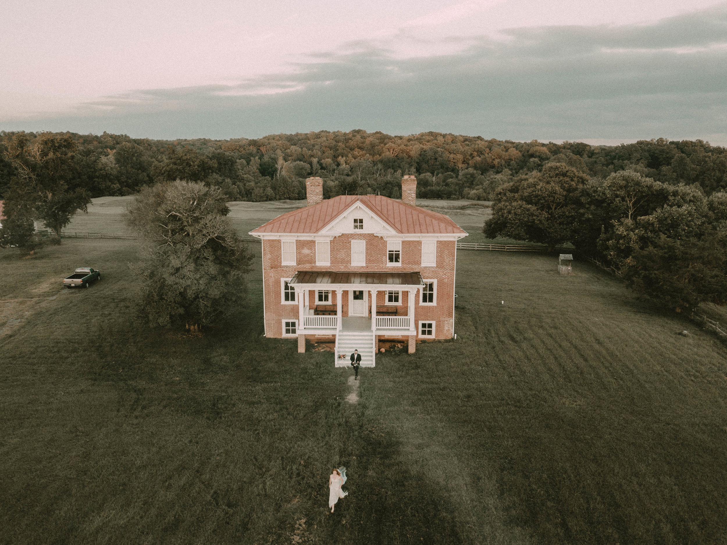 Drone shot of woman walking to farmhouse