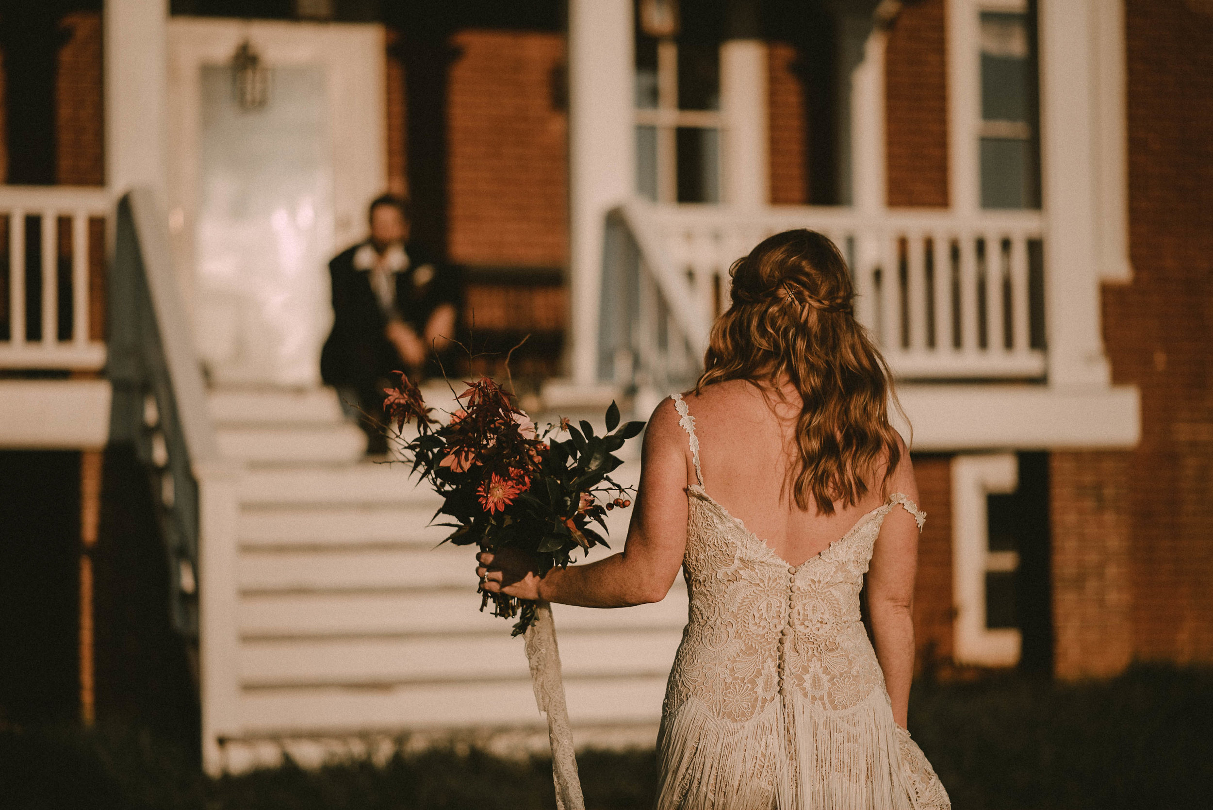 Bride approaching groom on porch