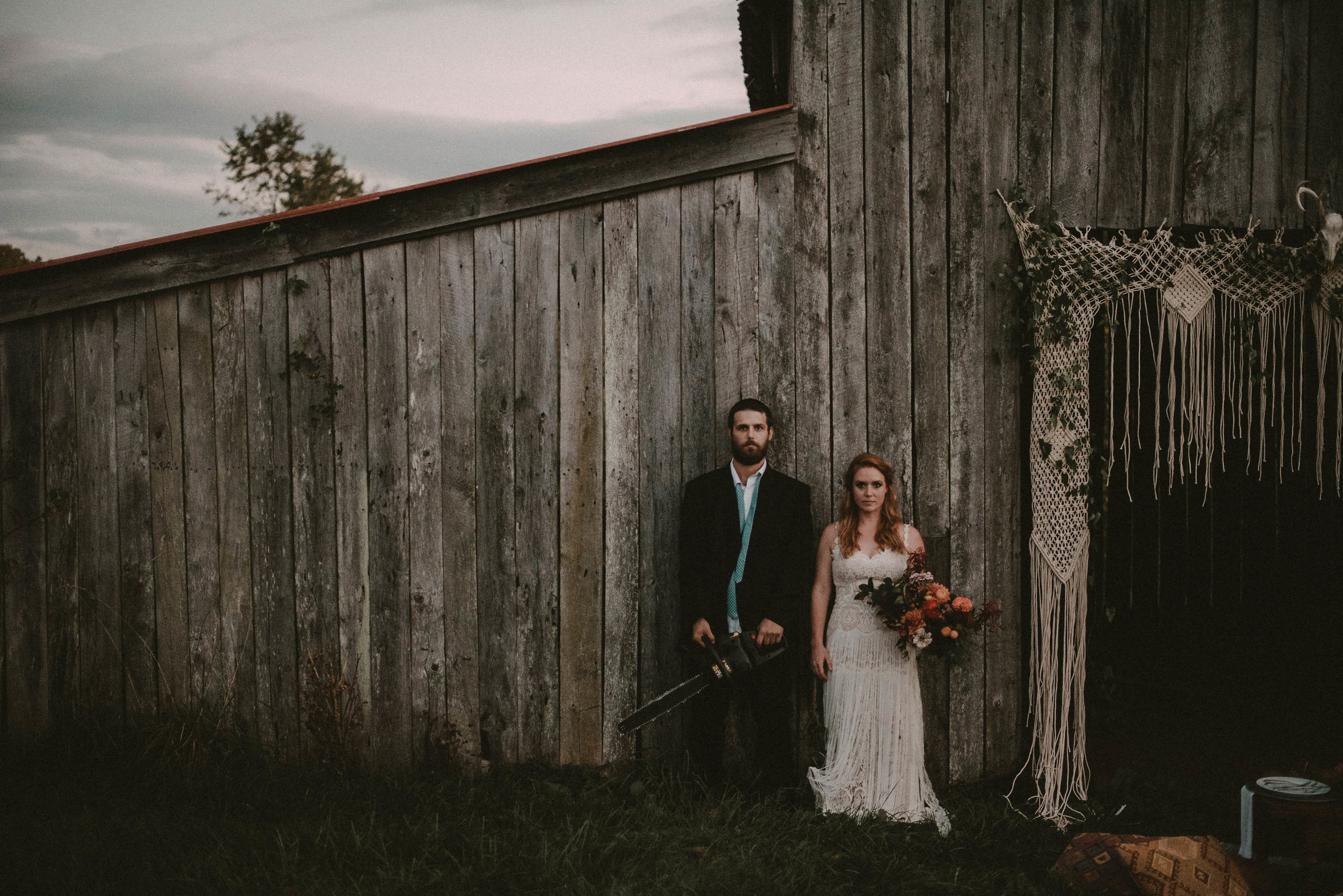 Bride and groom against old barn
