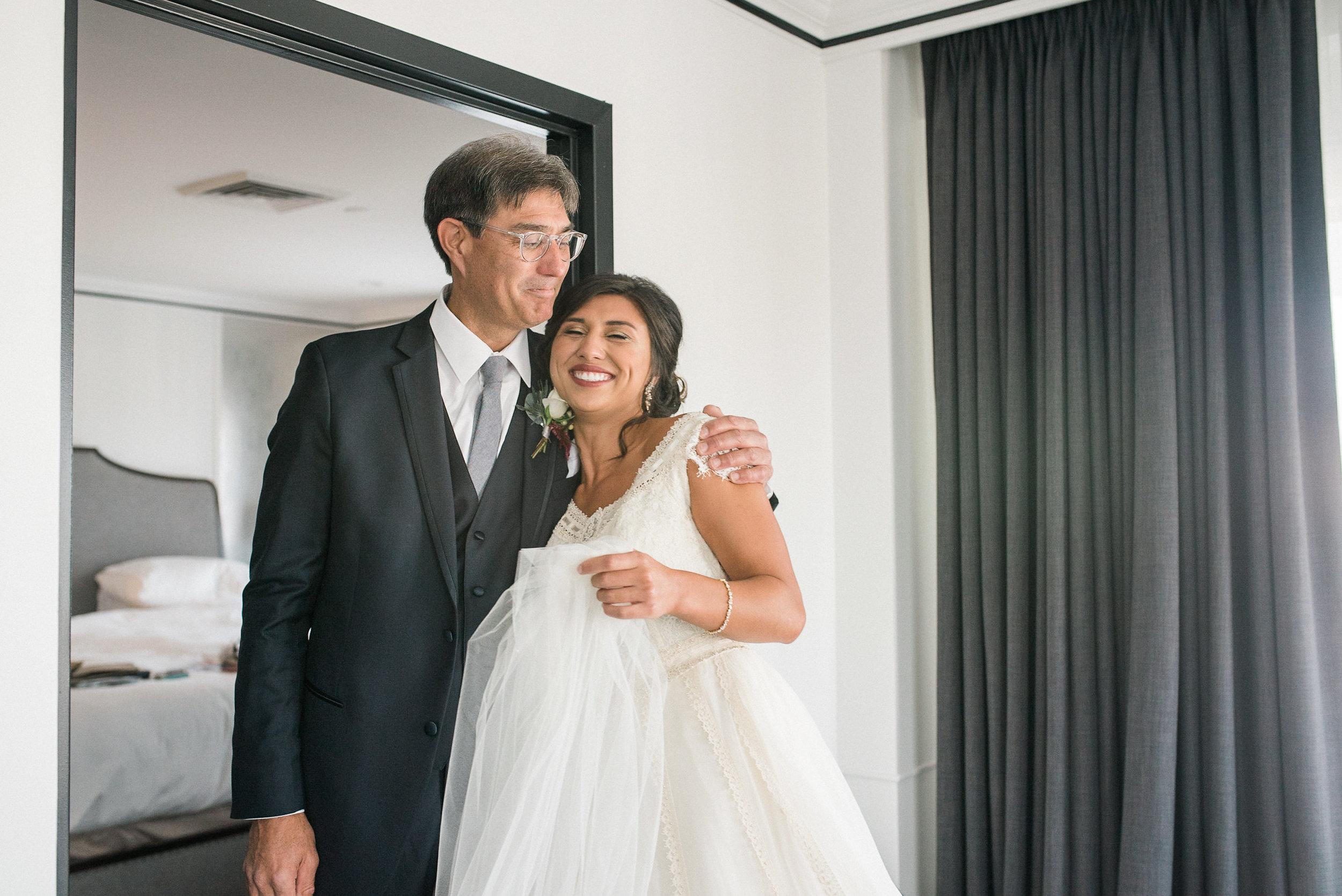 Bride hugging father in hotel room