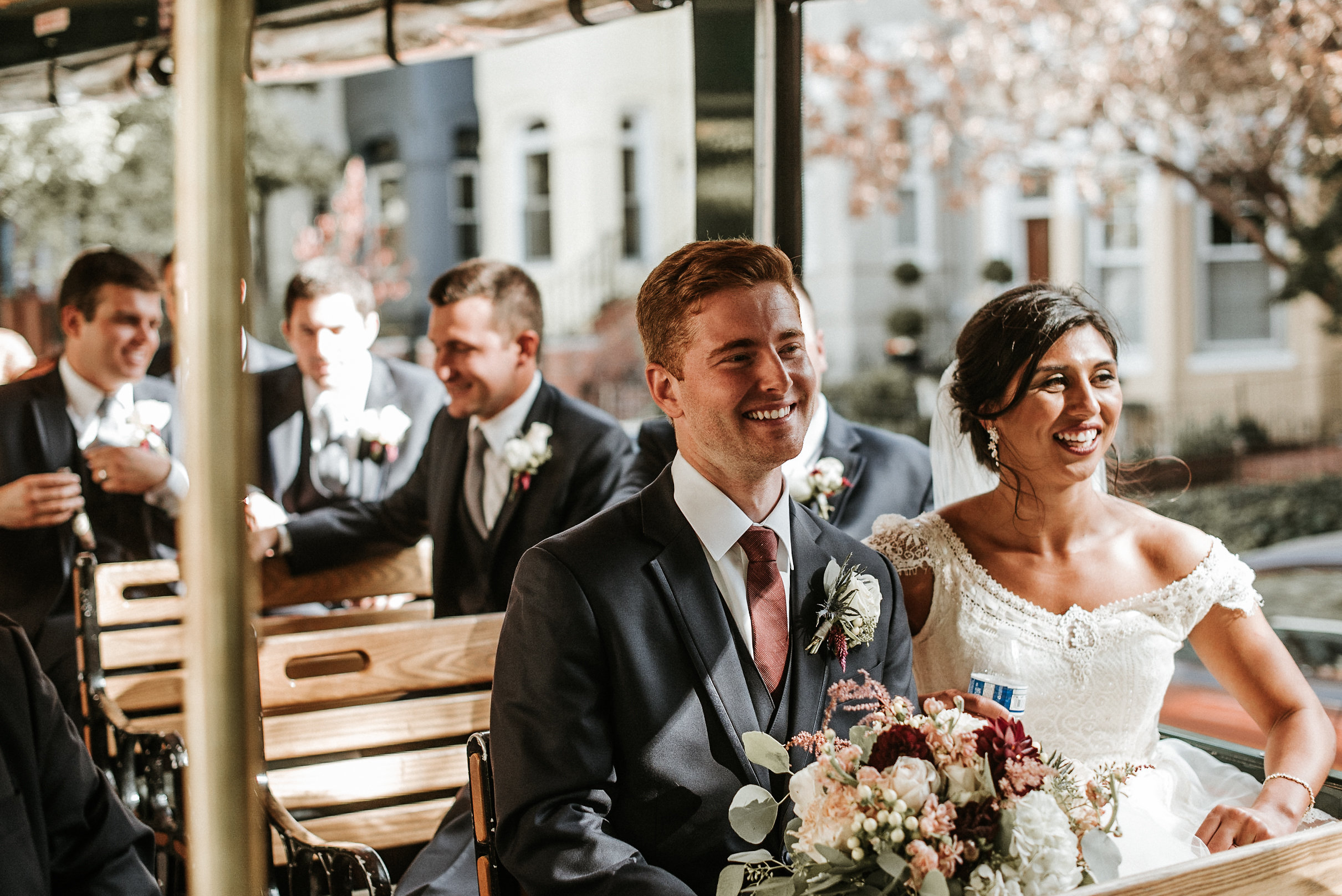 Bride and groom smiling on trolley