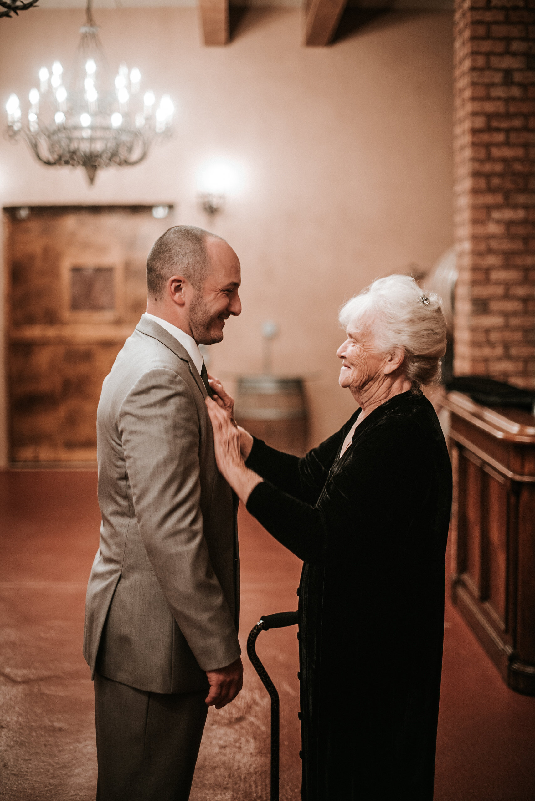 Grandmother straightening groom's tie