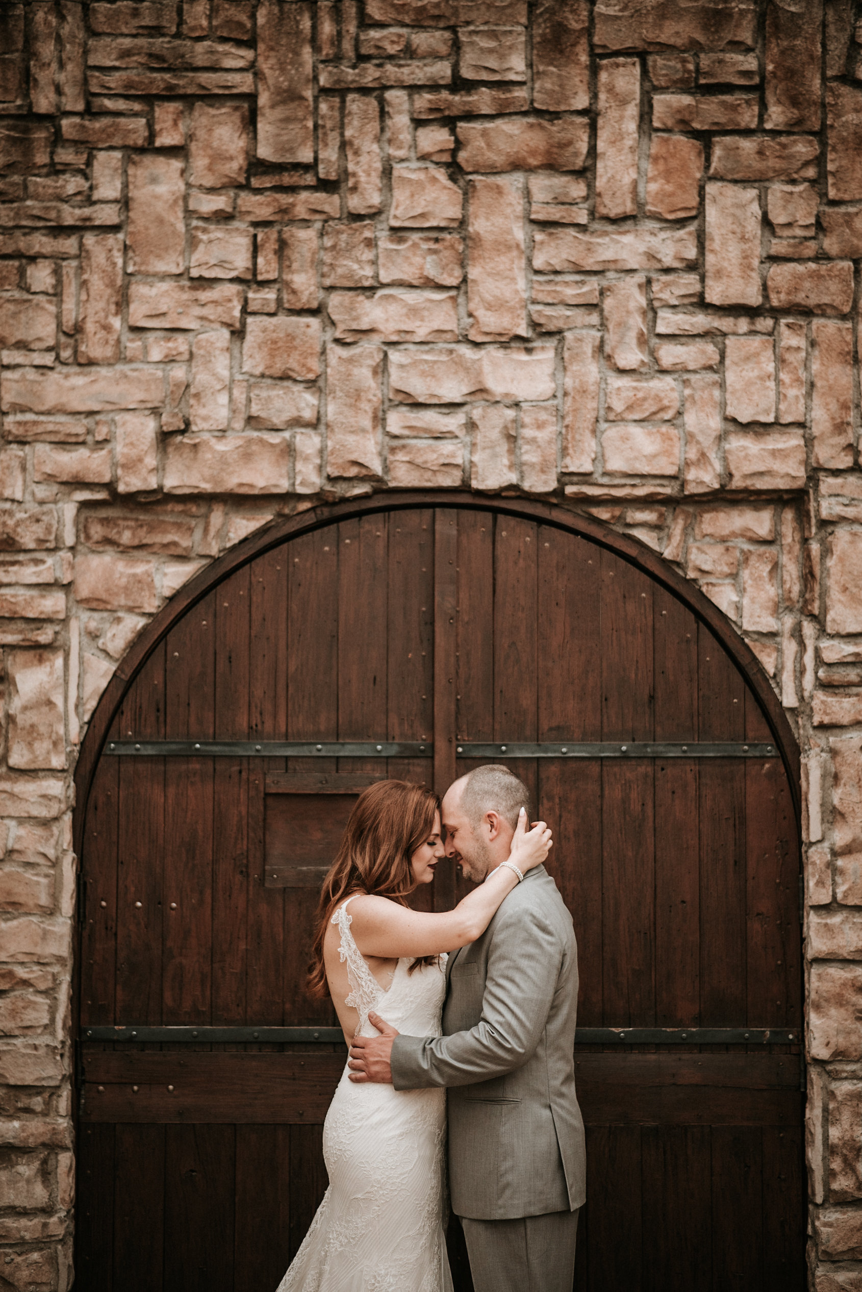 Bride and groom embracing in front of door