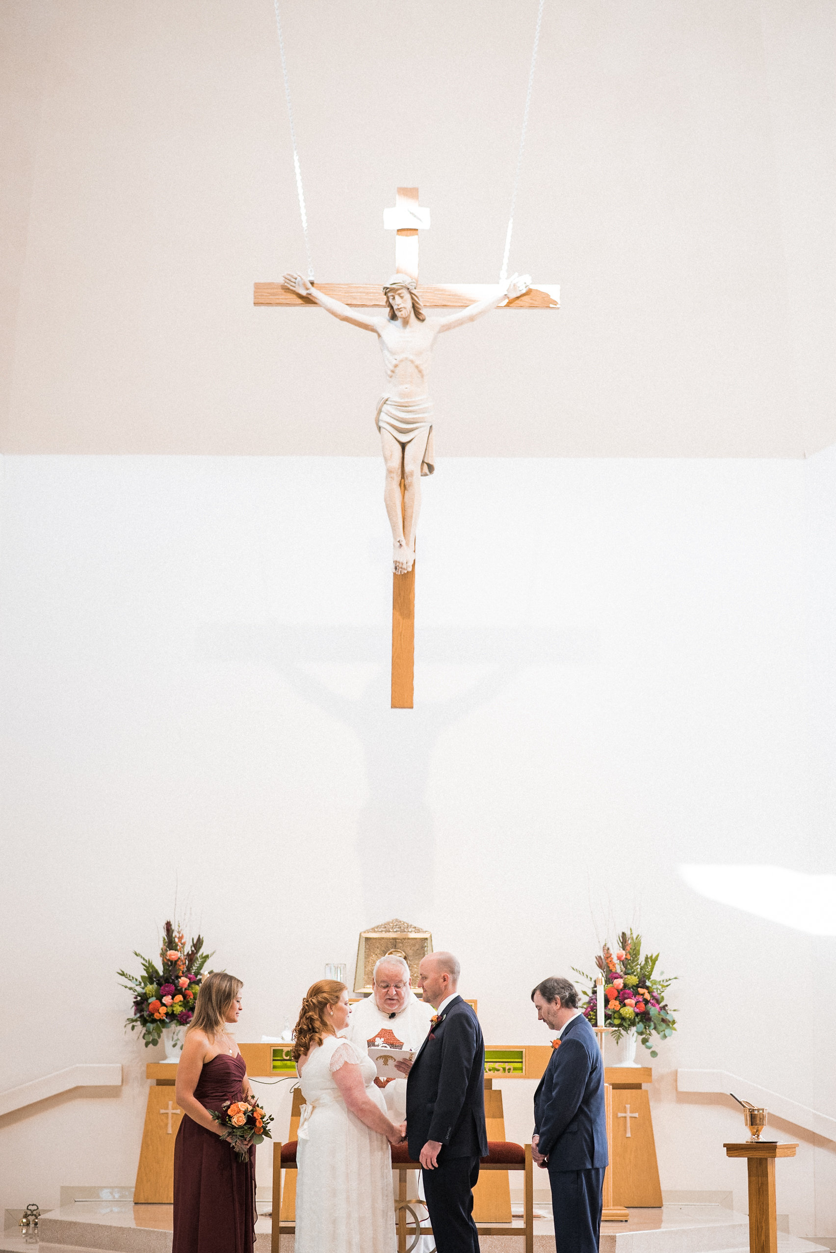 Bride and groom under crucifix