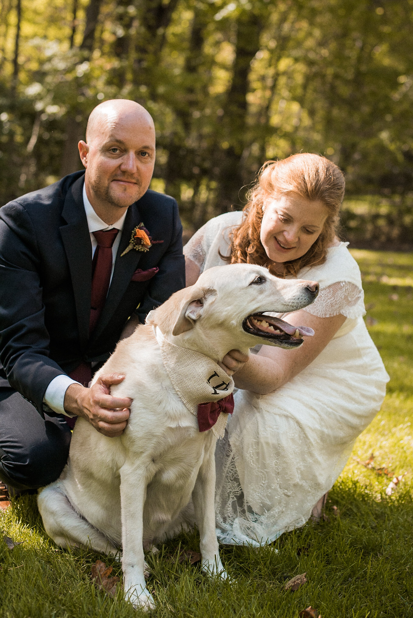 Bride and groom petting dog