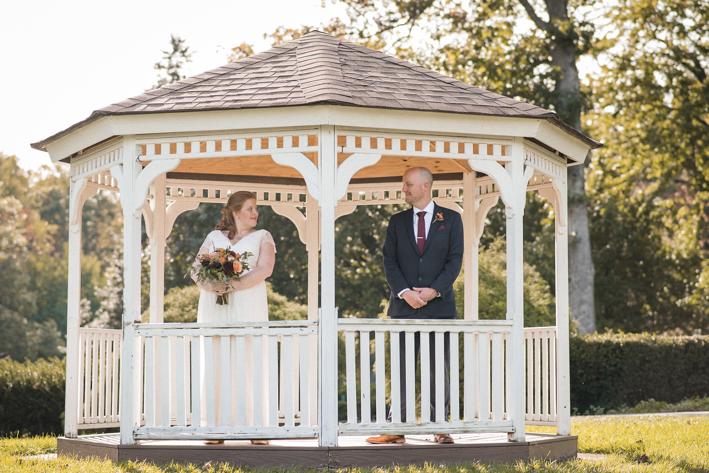 Bride and groom standing in gazebo