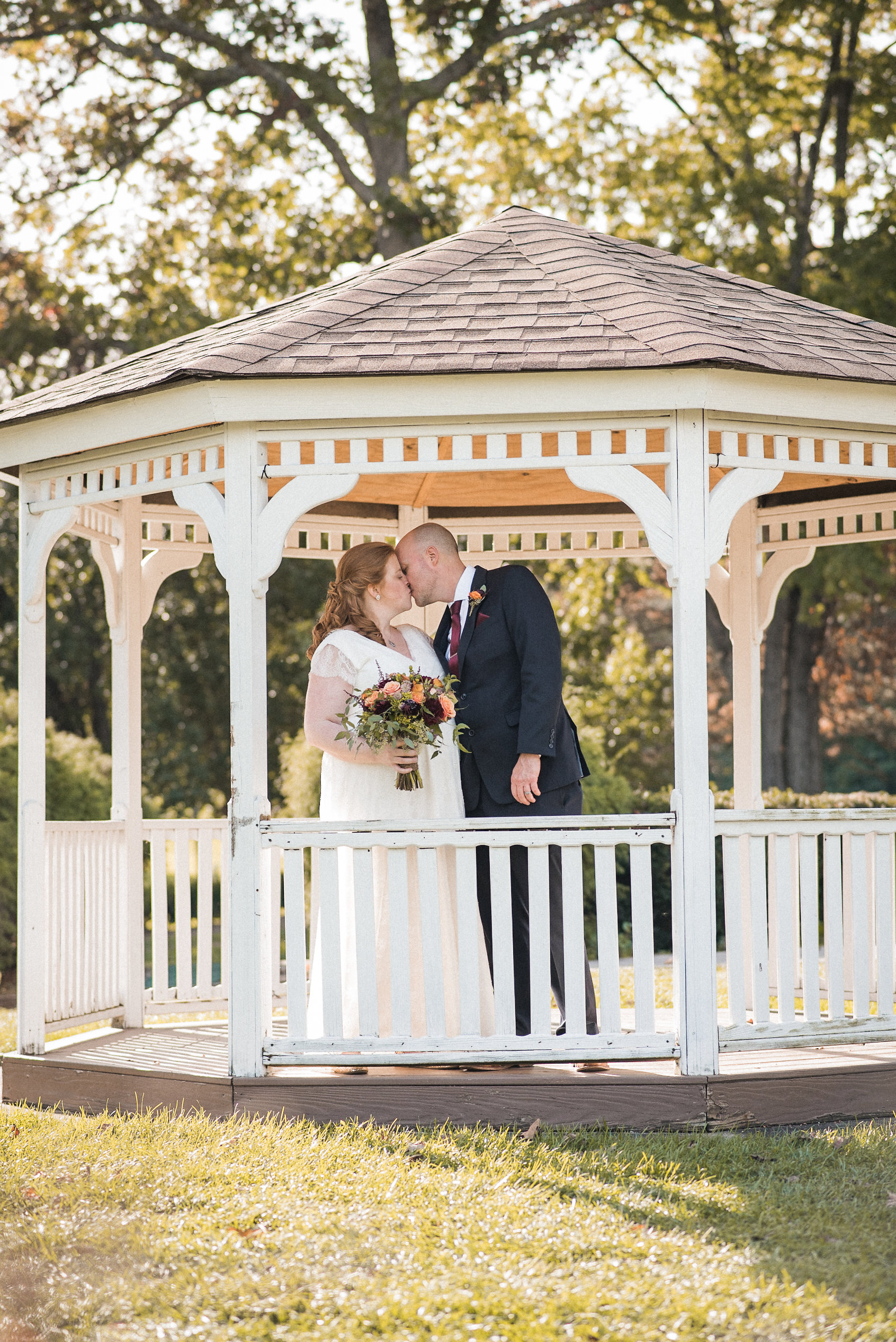 Bride and groom kissing in gazebo
