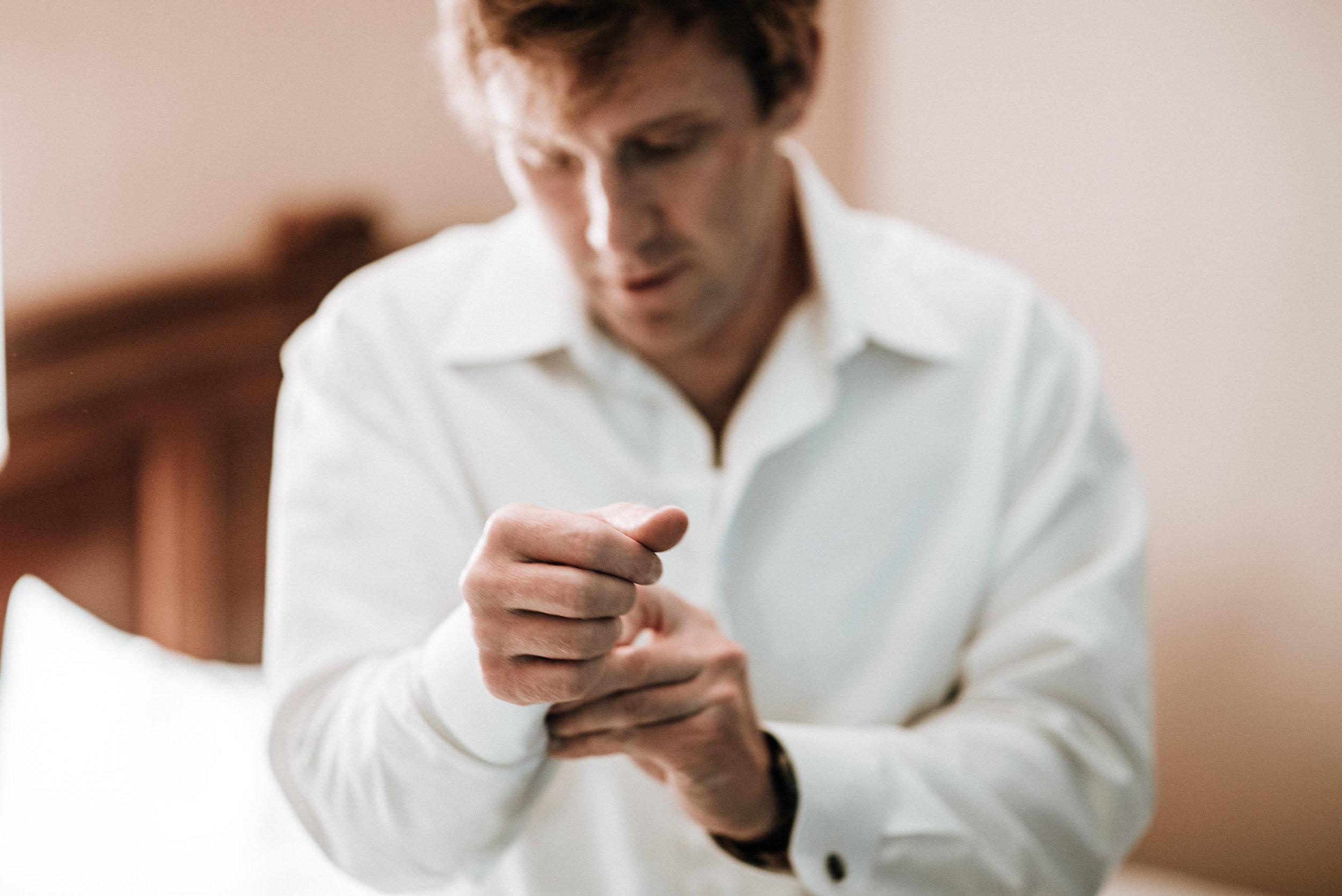 Man buttoning cuffs