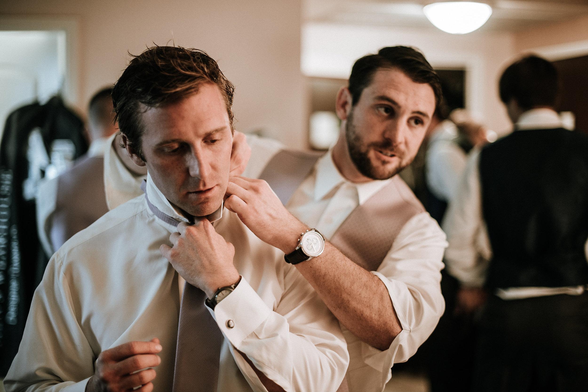 Groomsmen helping groom with tie