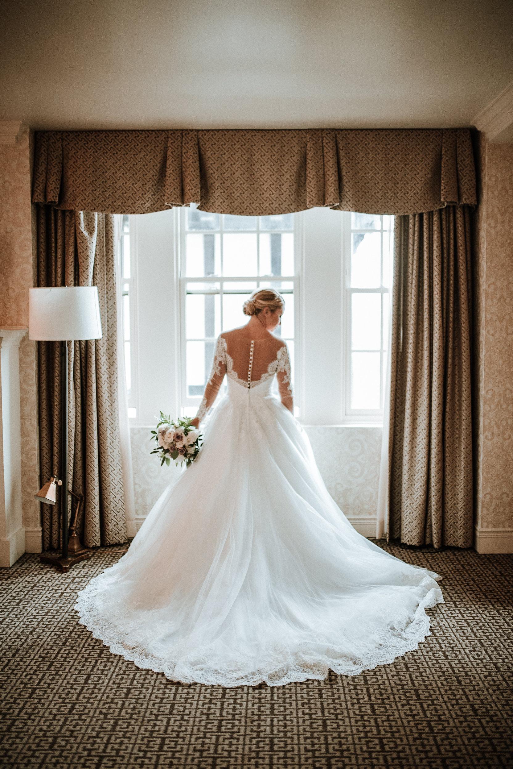 Bride standing in front of windows