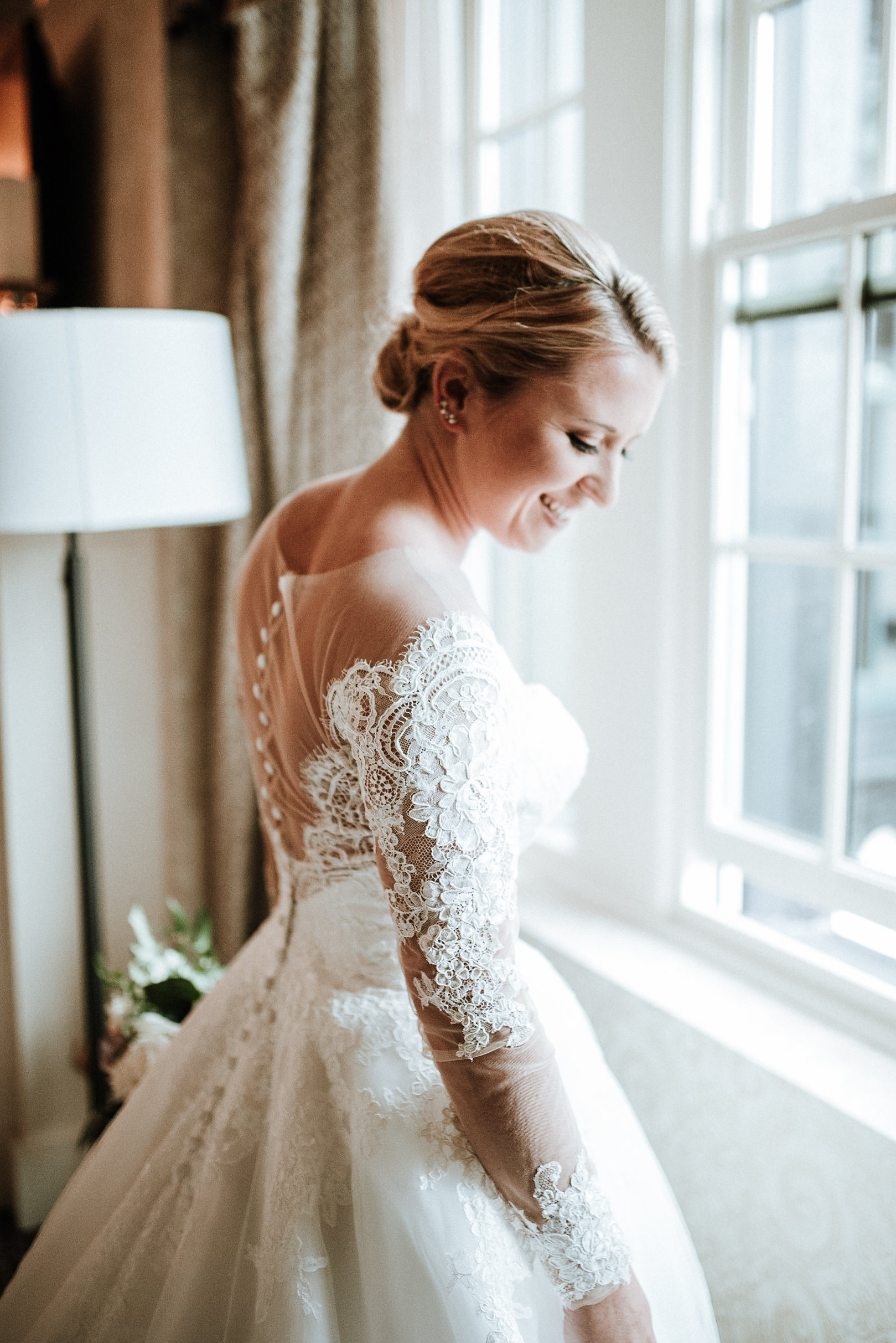 Bride smiling at window
