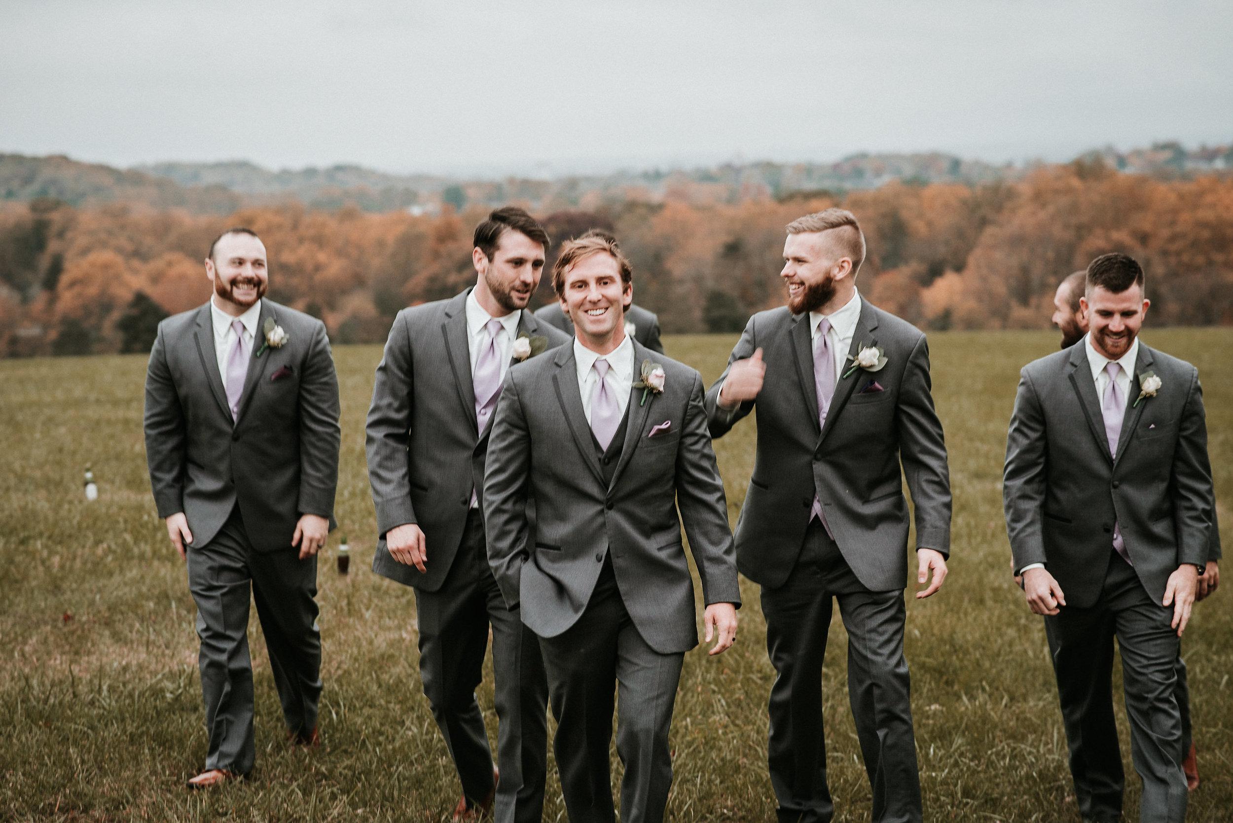 Groom and groomsmen walking through field
