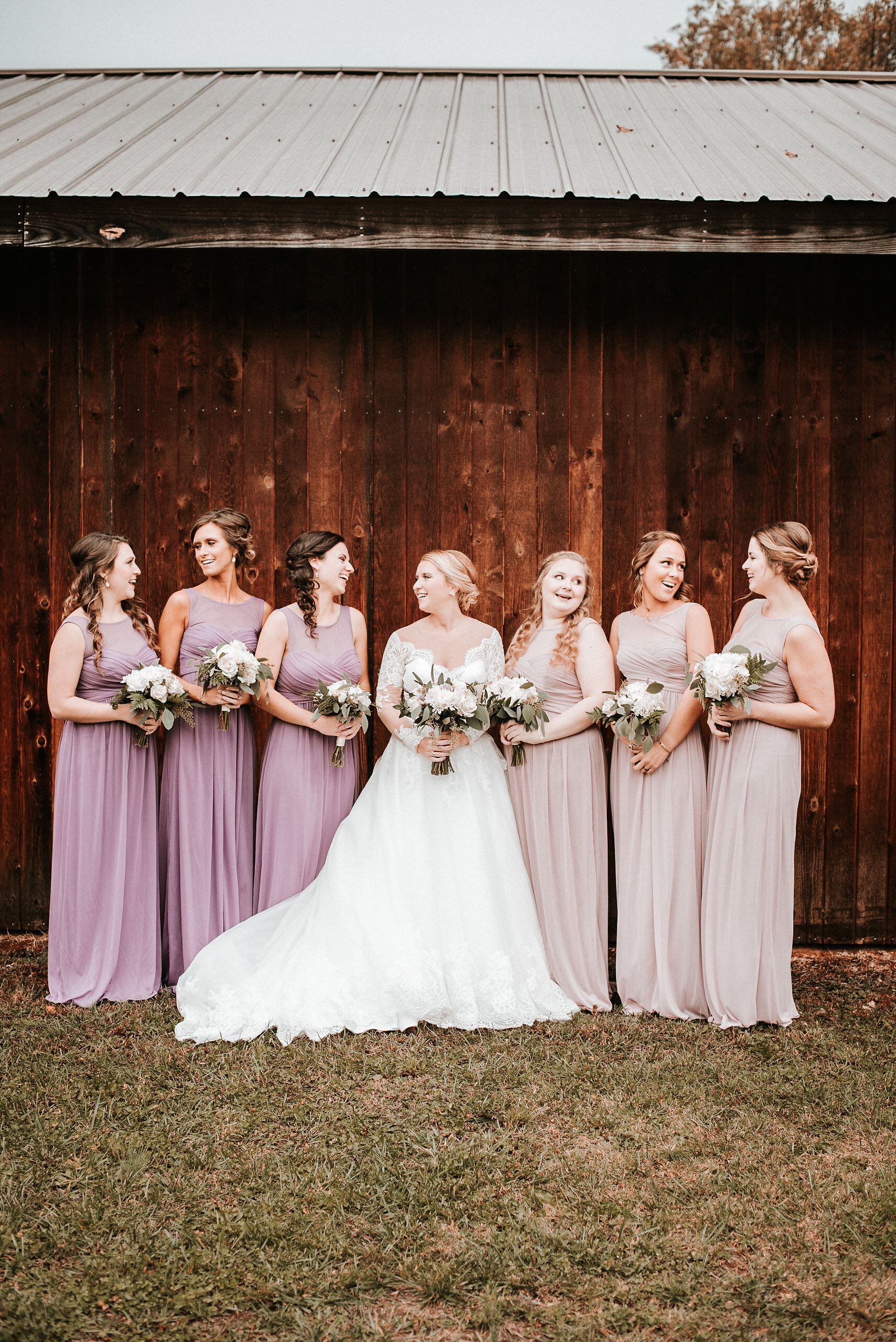 Bride and bridesmaids standing against barn