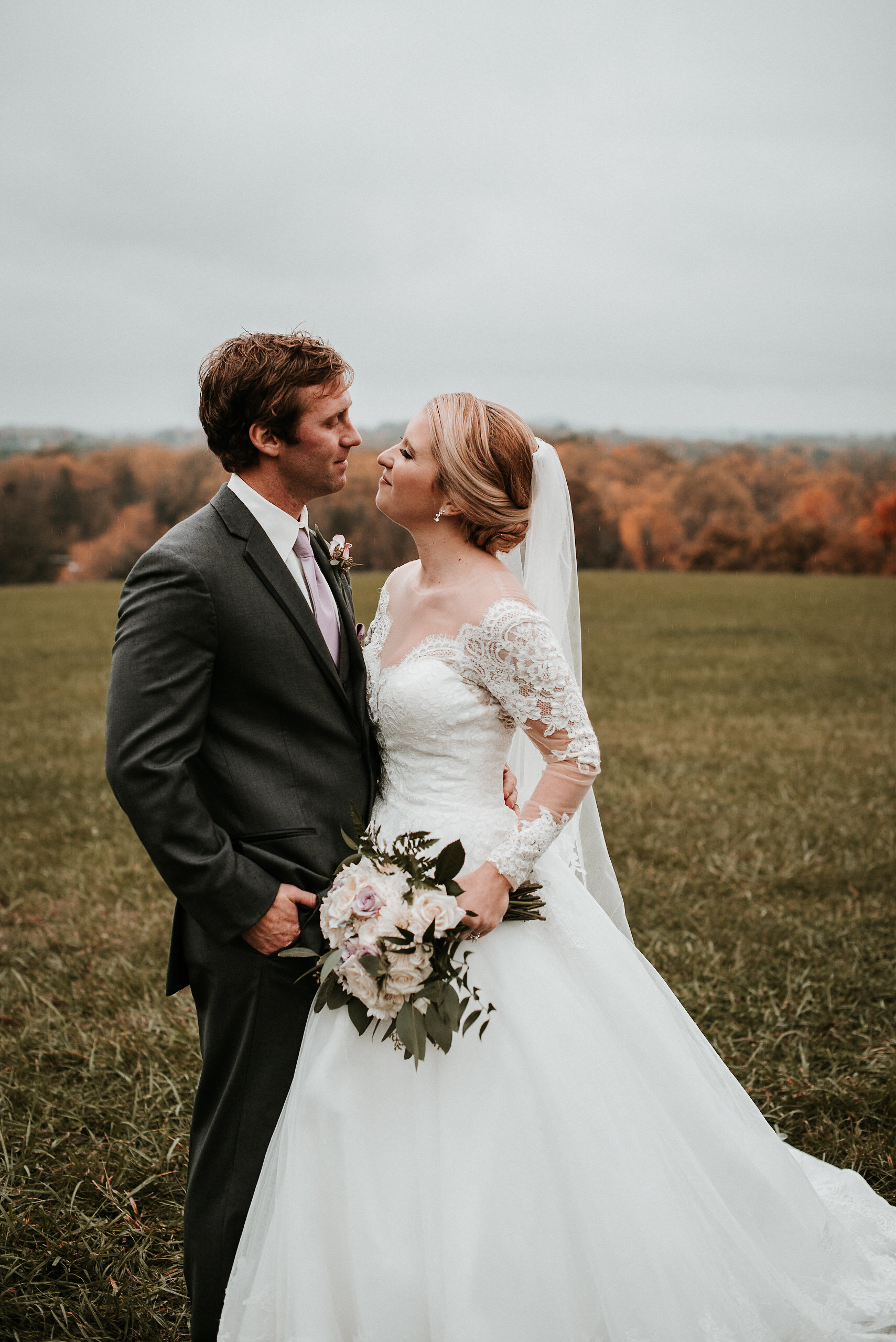 Bride and groom kissing in field