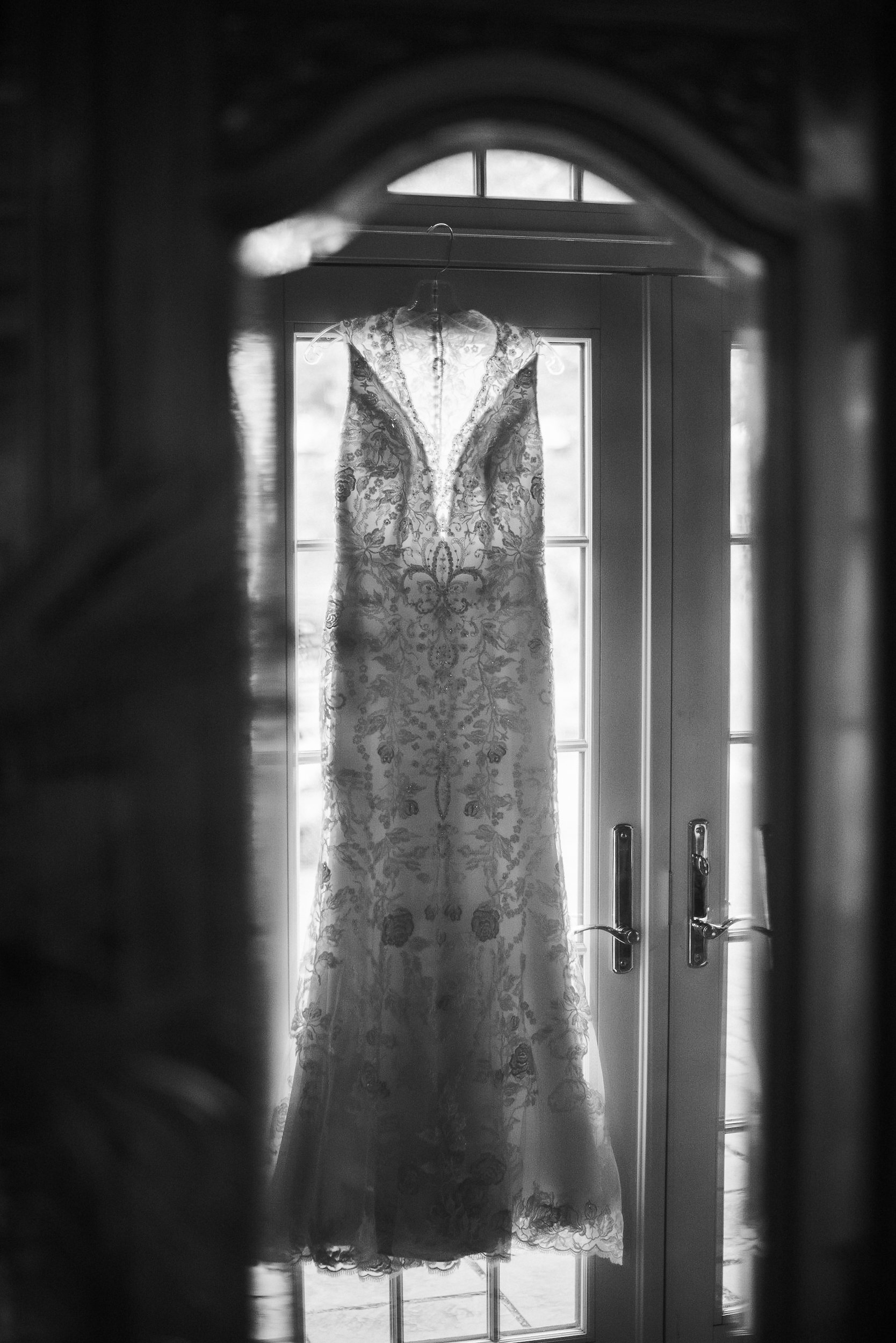Wedding dress hanging on door in black and white
