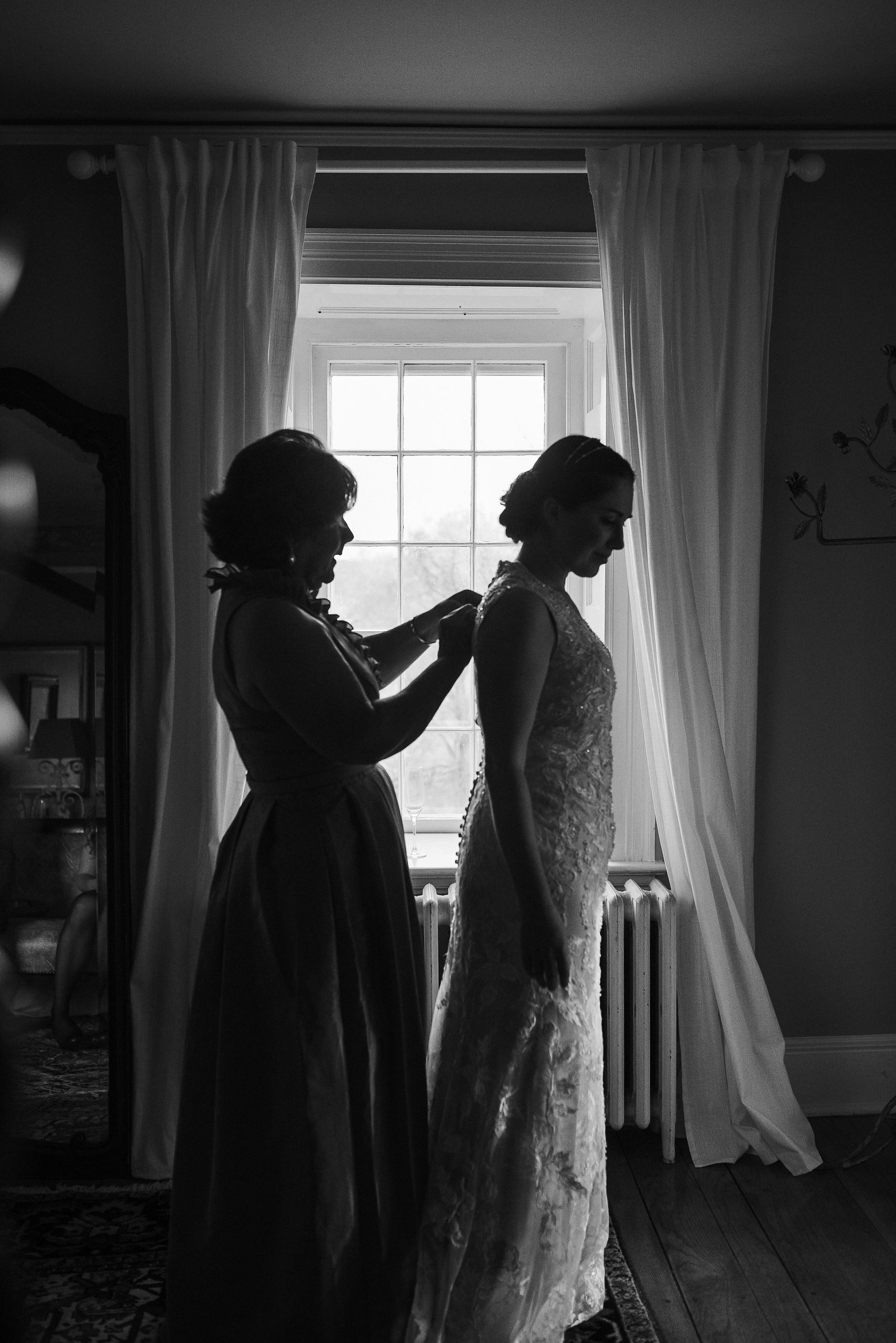 Mother zipping up bride's dress