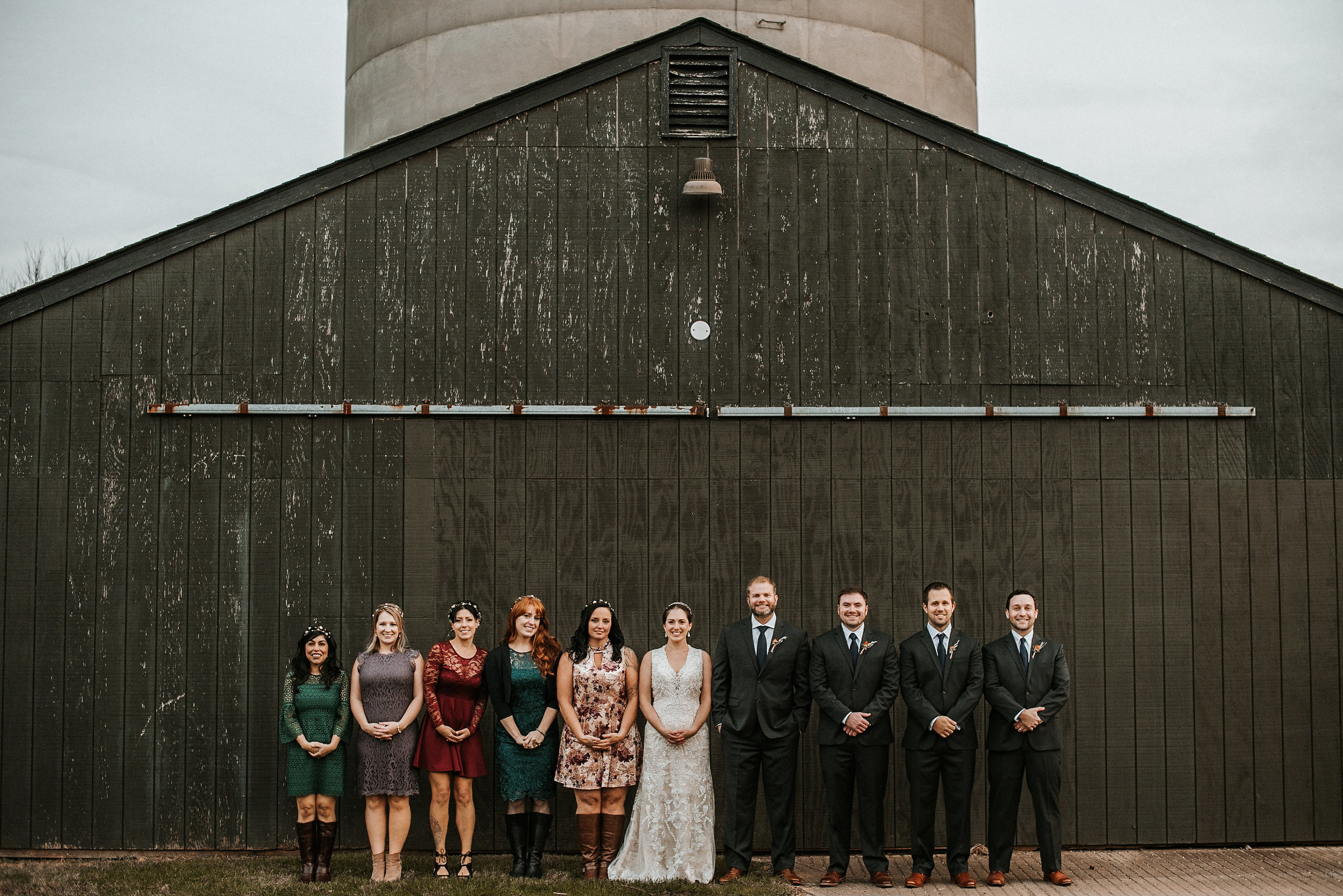 Bridal party against black barn