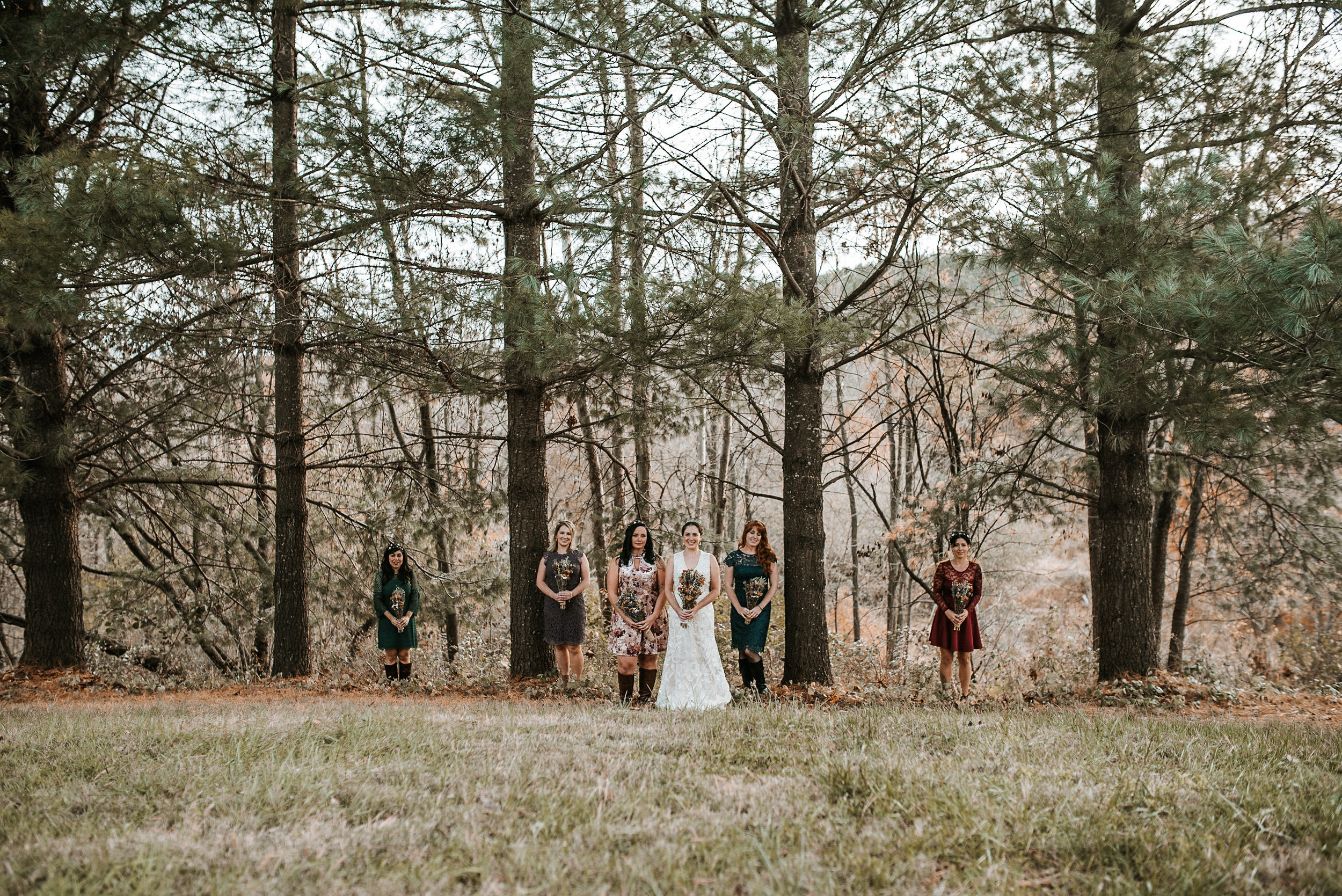 Bride and bridesmaids standing in tree line