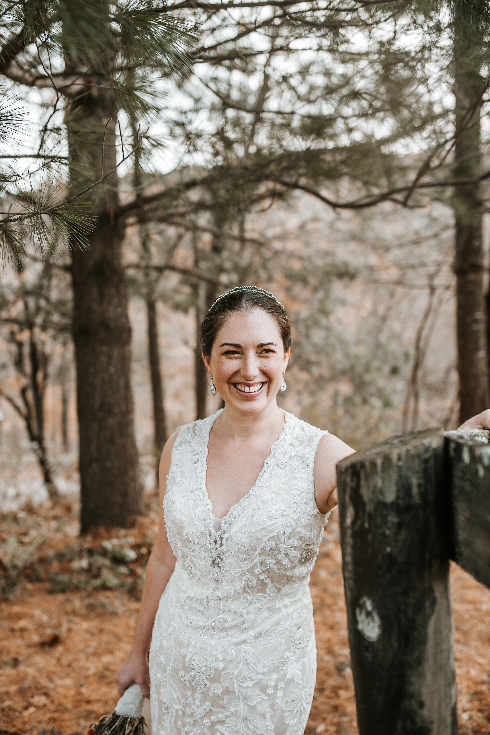 Bride standing near wooden post