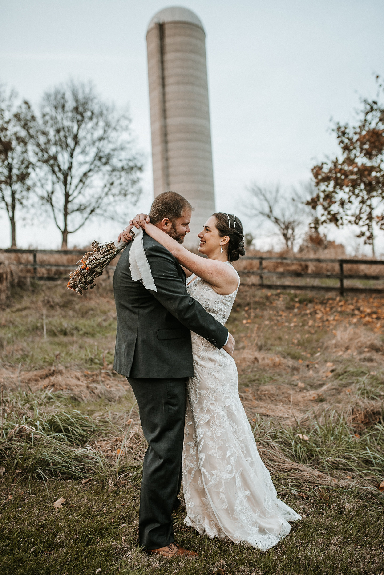 Bride and groom embracing in front of silo