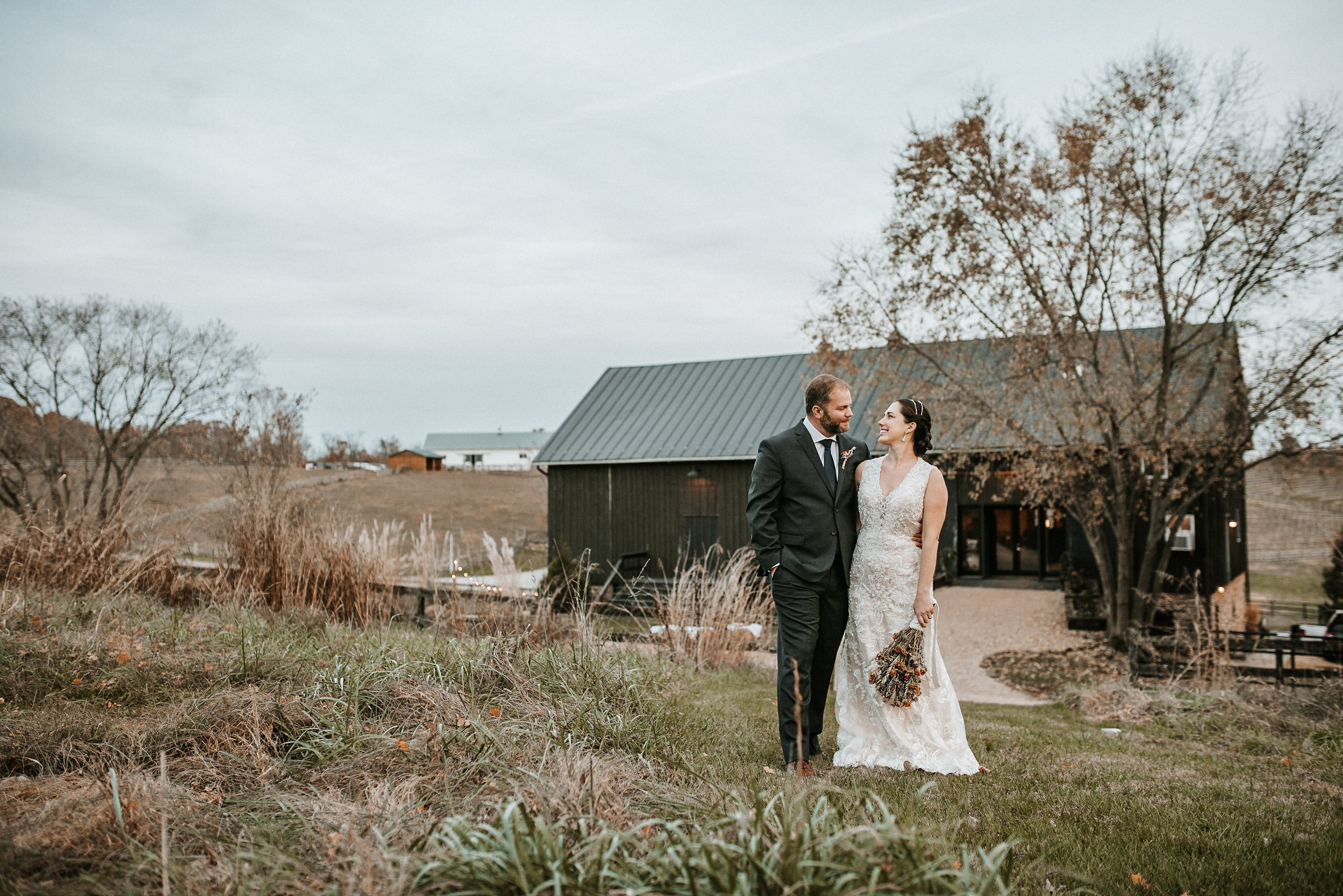 Bride and groom in front of black barn