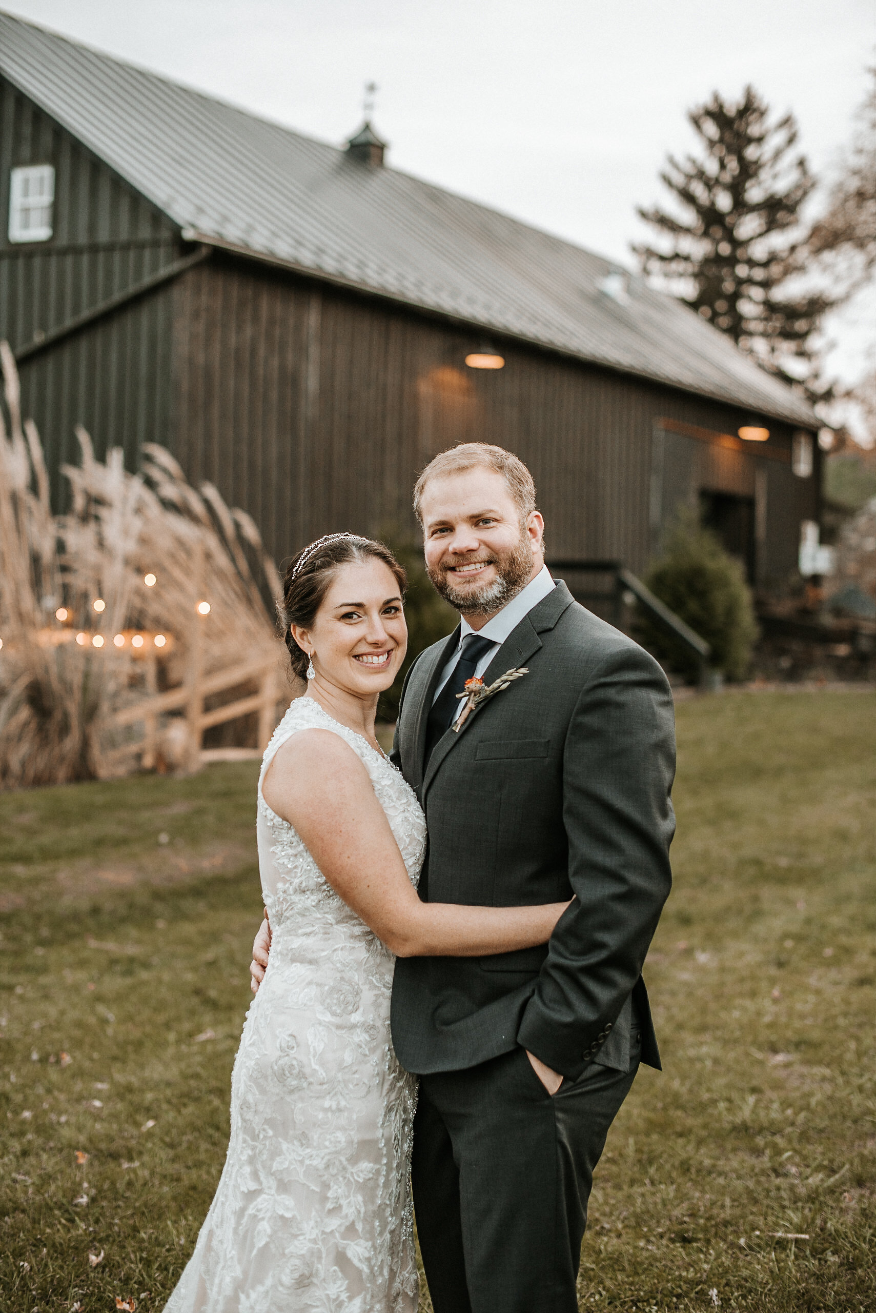 Bride and groom hugging in front of barn