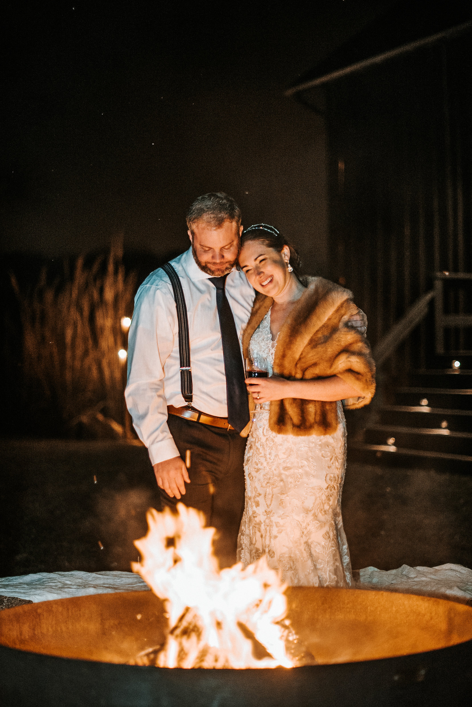 Bride and groom standing by fire