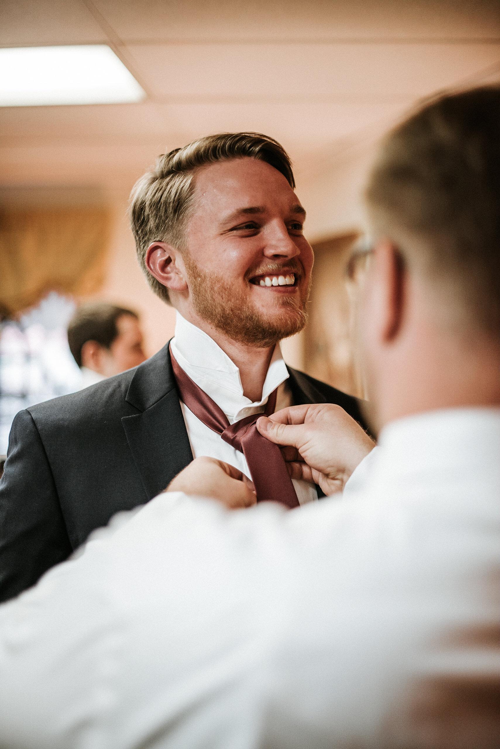 Groom getting tie tied before wedding