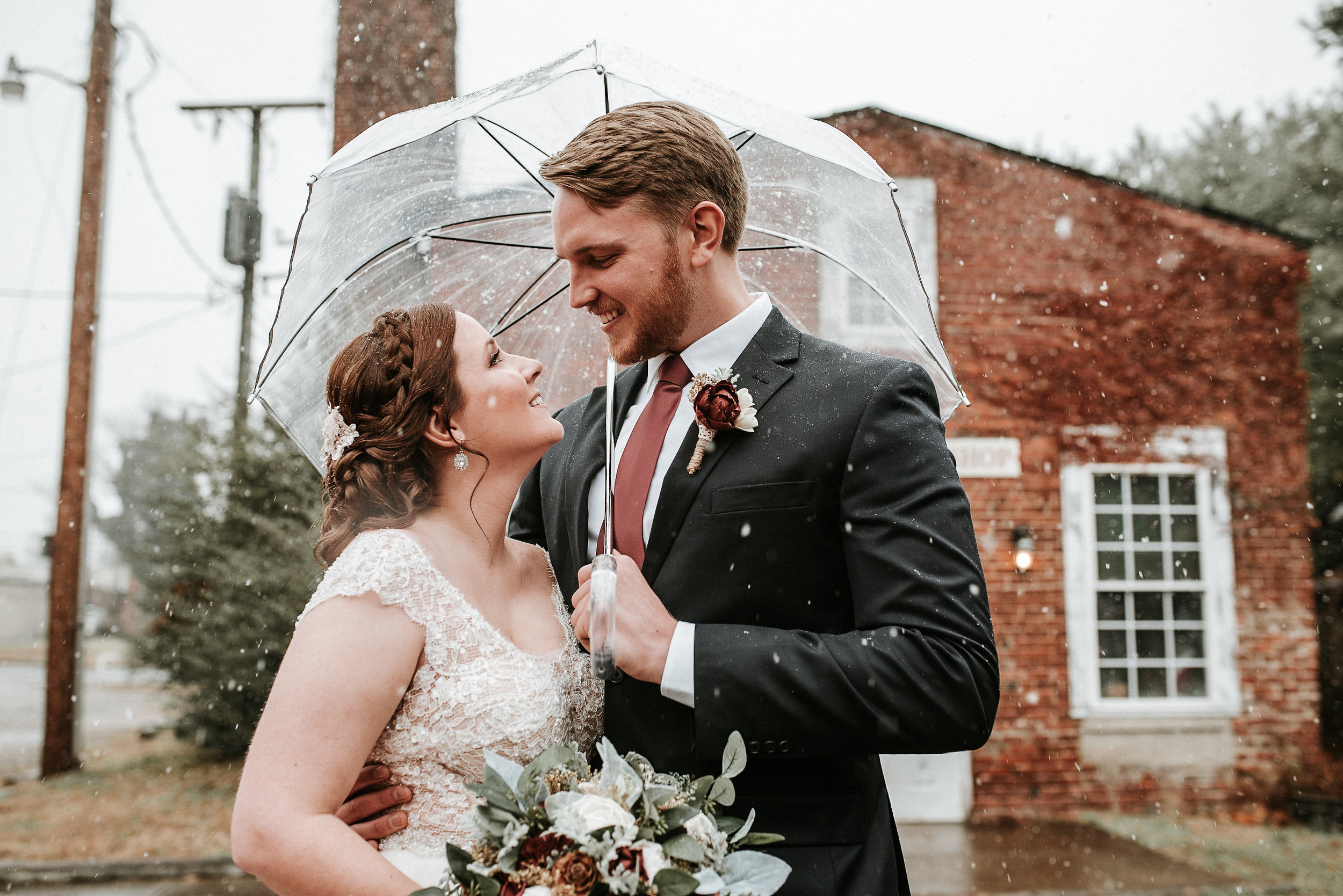 Bride and groom standing under umbrella