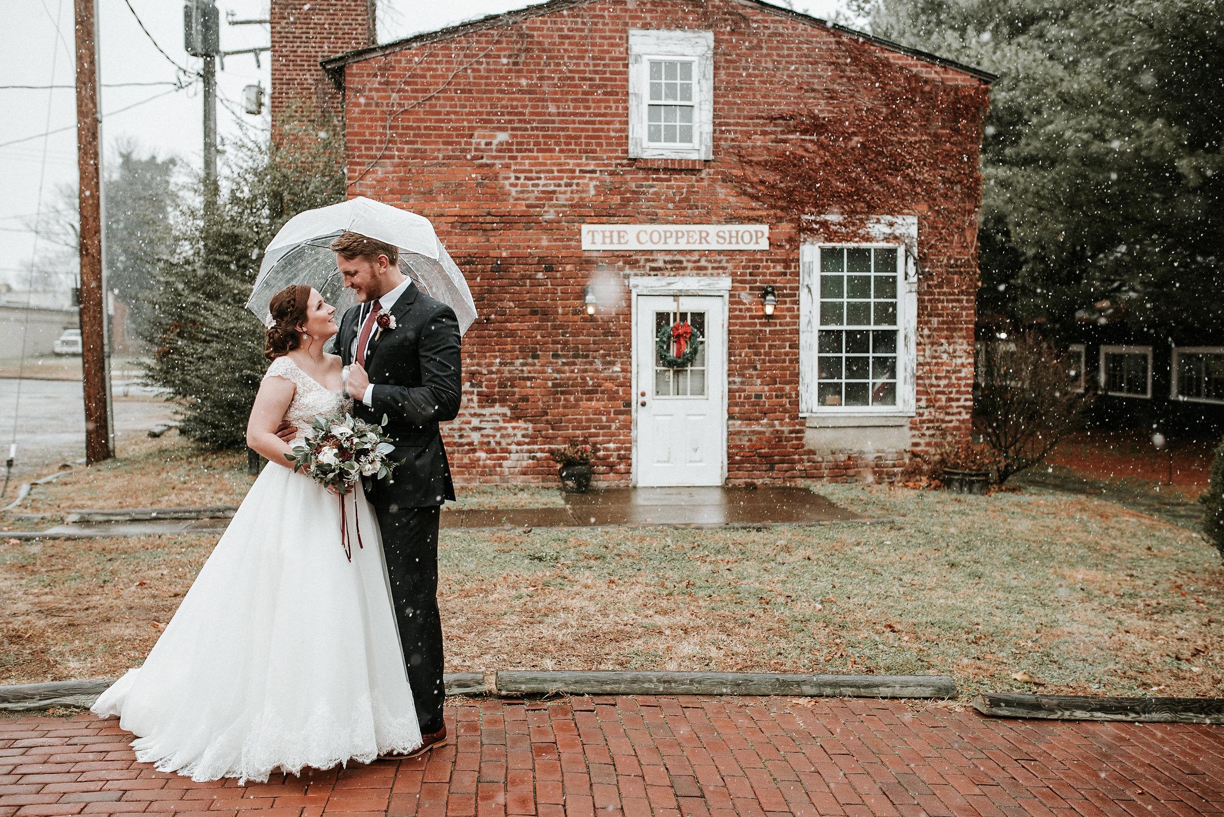 Bride and groom on brick sidewalk in snow