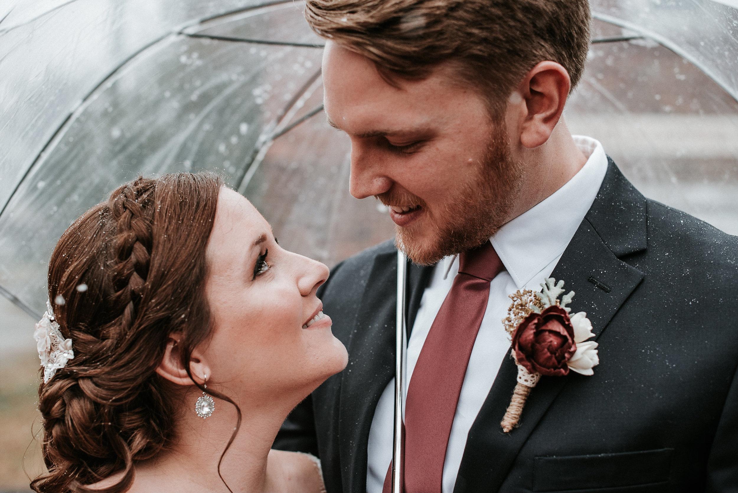 Bride and groom cozied up under umbrella