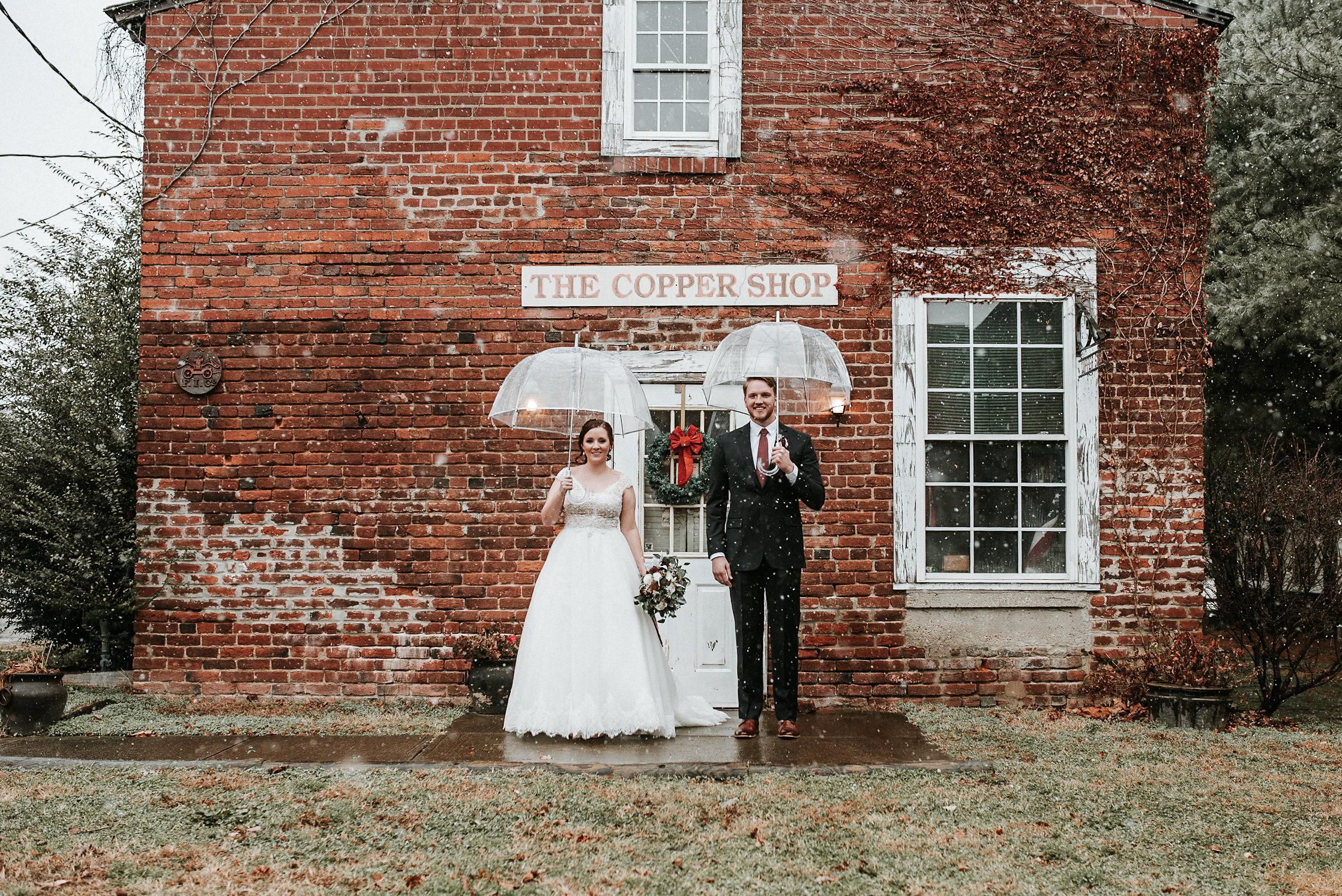 Bride and groom standing under umbrellas
