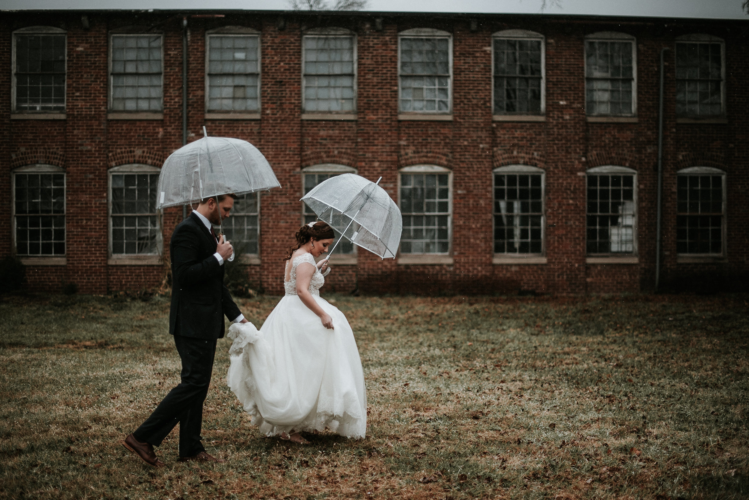 Bride and groom walking across lawn in front of factory