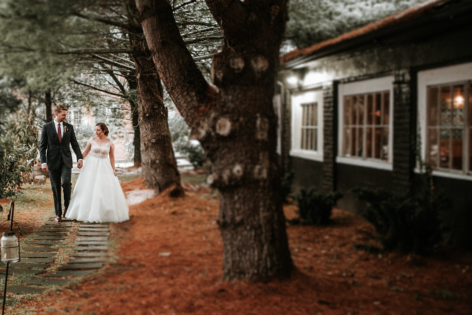 Bride and groom walking on path under pine trees