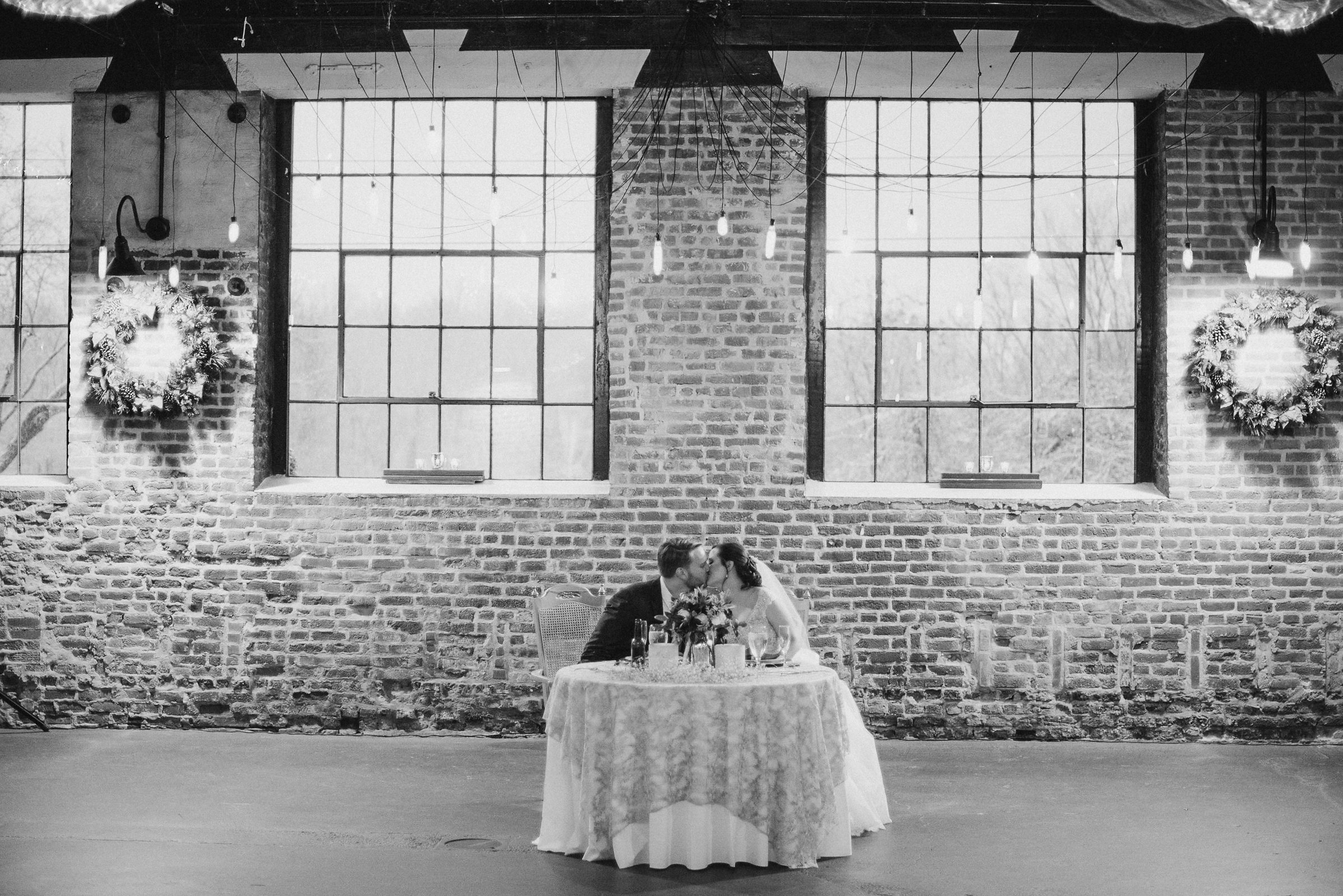 Bride and groom kissing at table